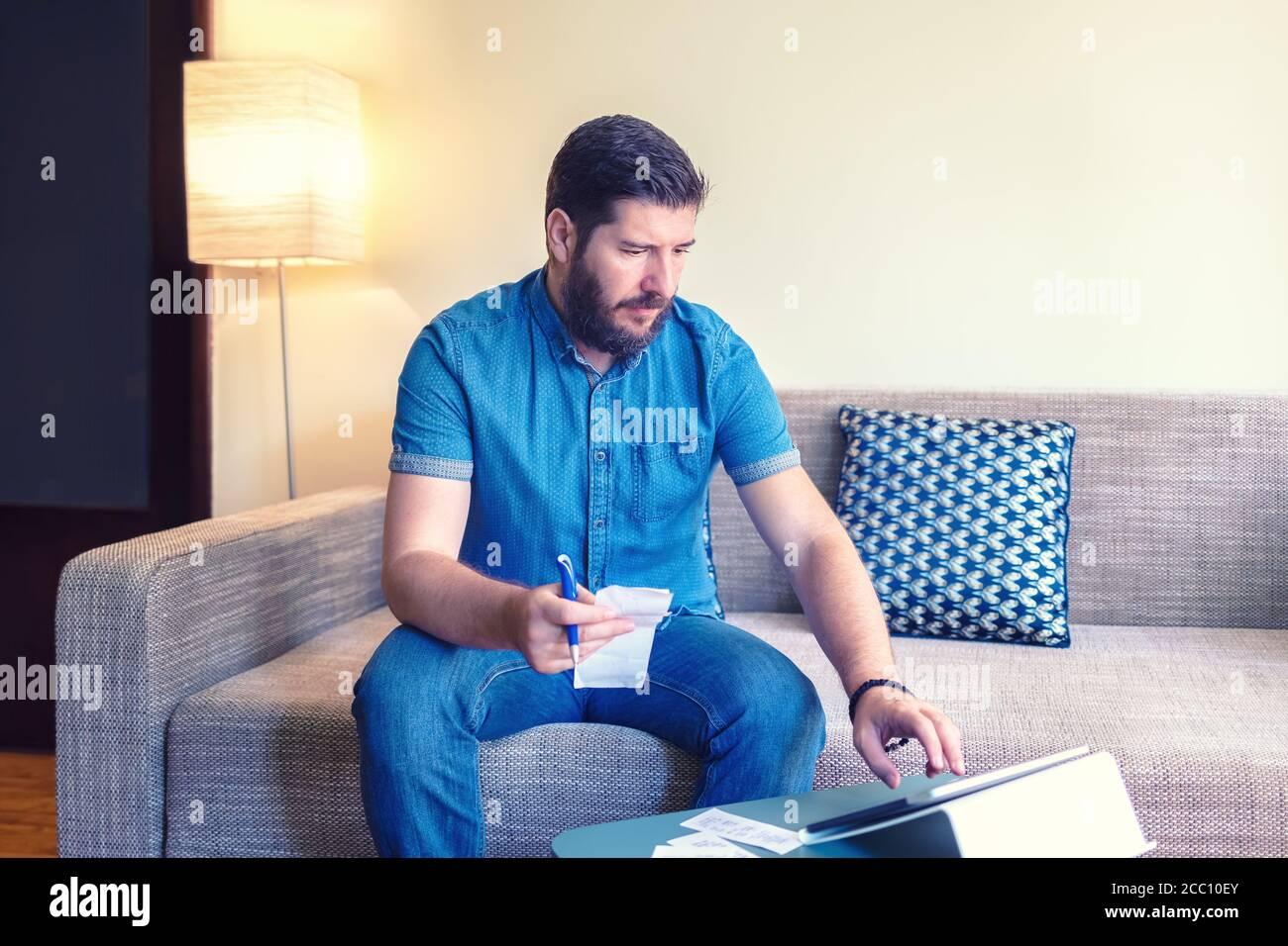 Mature man doing home finance online using digital tablet Stock Photo