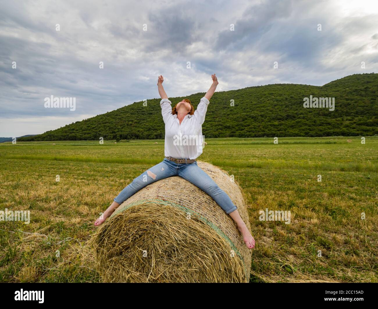 Redhaired woman riding hay haystack acting free person Stock Photo