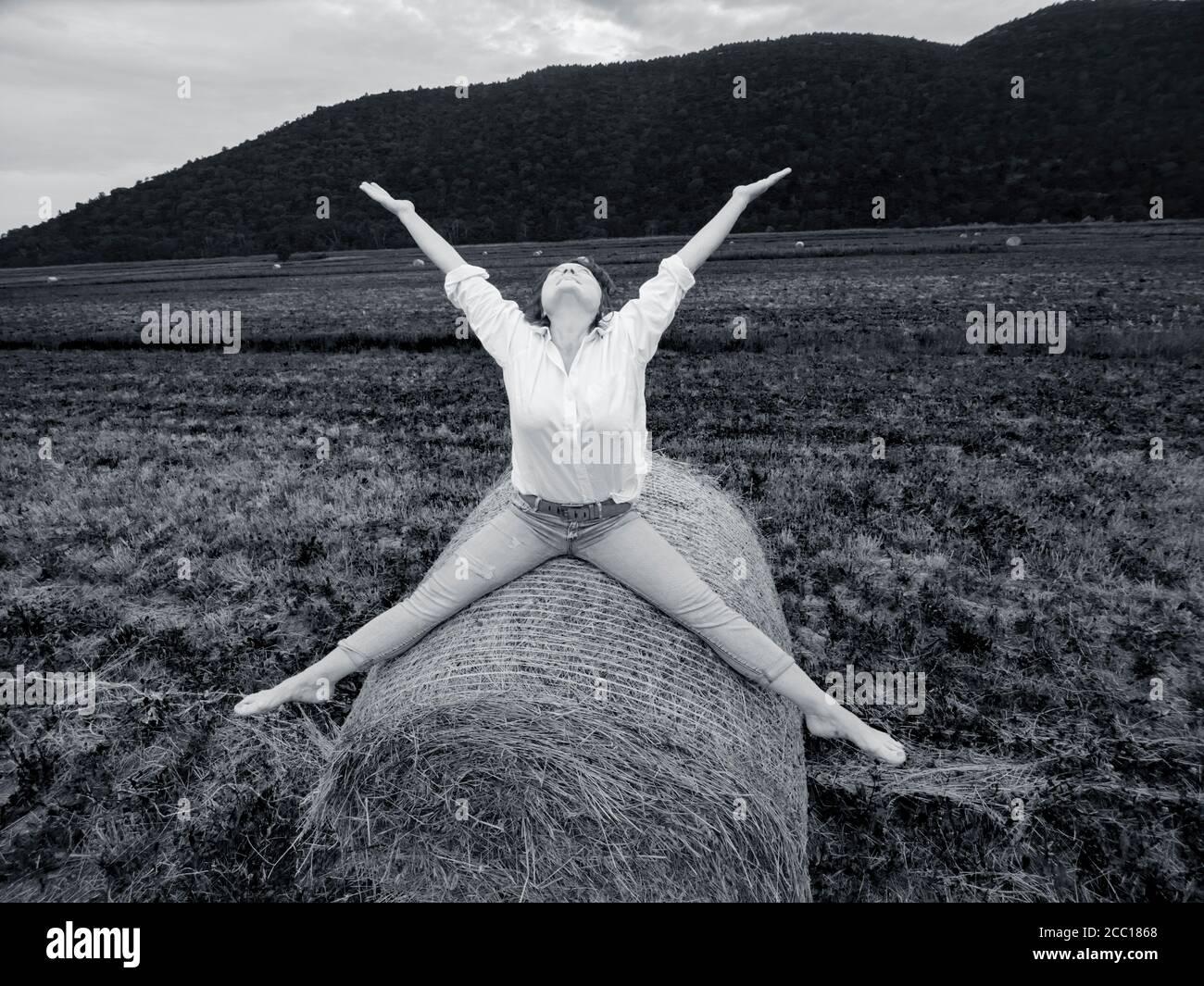 Woman riding hay haystack in retro monochrome b&w Black and White Stock Photo