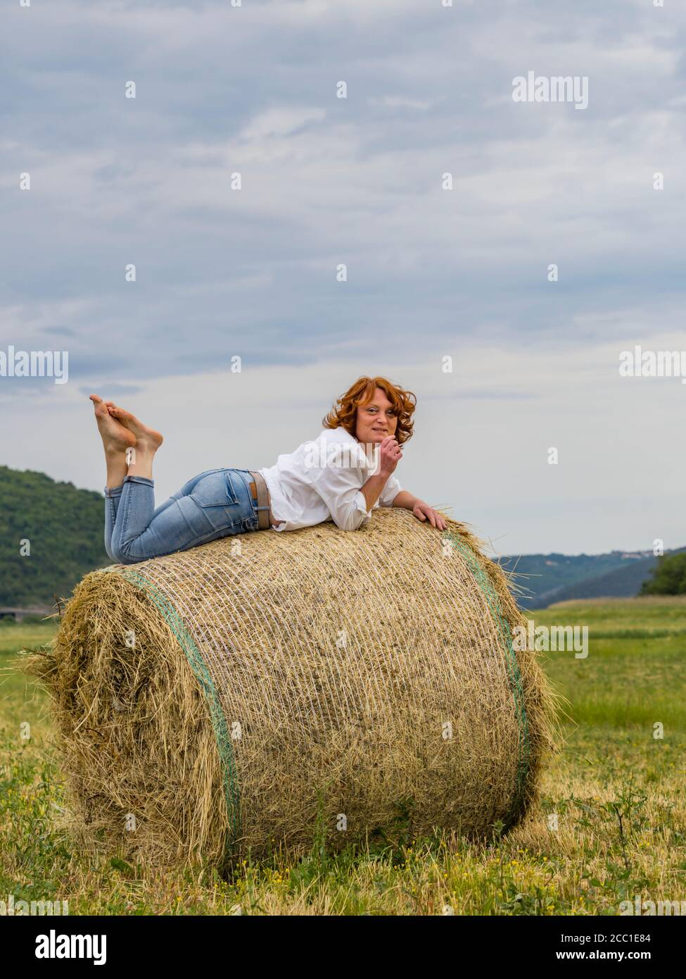Redhaired woman on hay haystack leisure Stock Photo