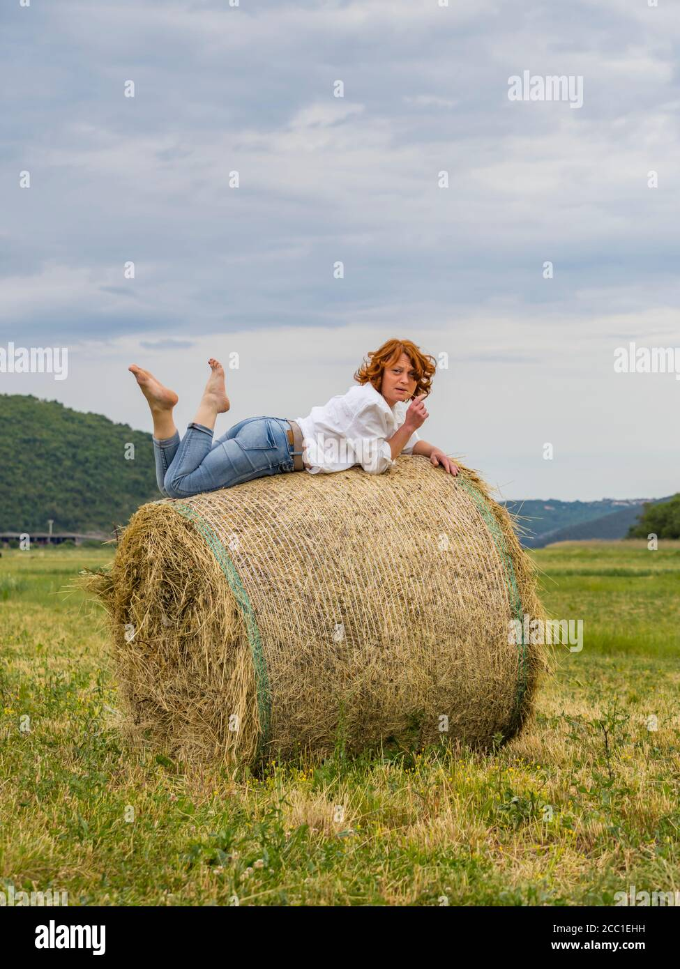 Redhaired woman on hay haystack leisure lazy Stock Photo