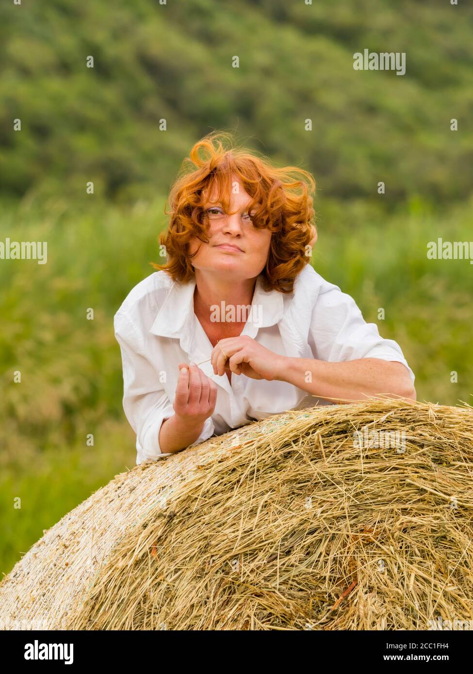 Redhaired woman on hay haystack portrait view Stock Photo