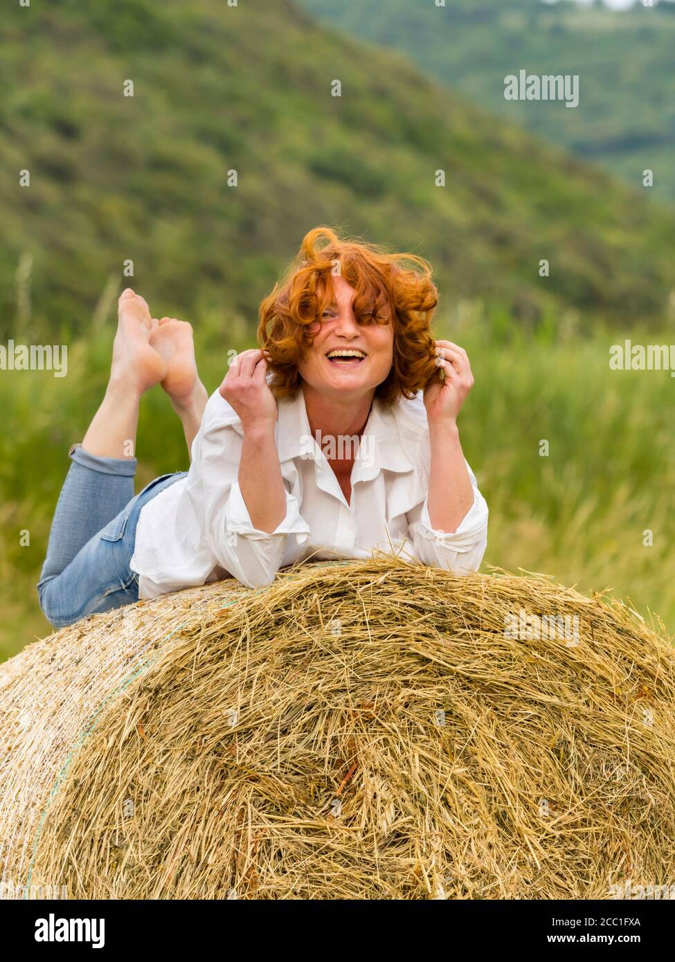 Redhaired woman on hay haystack Stock Photo