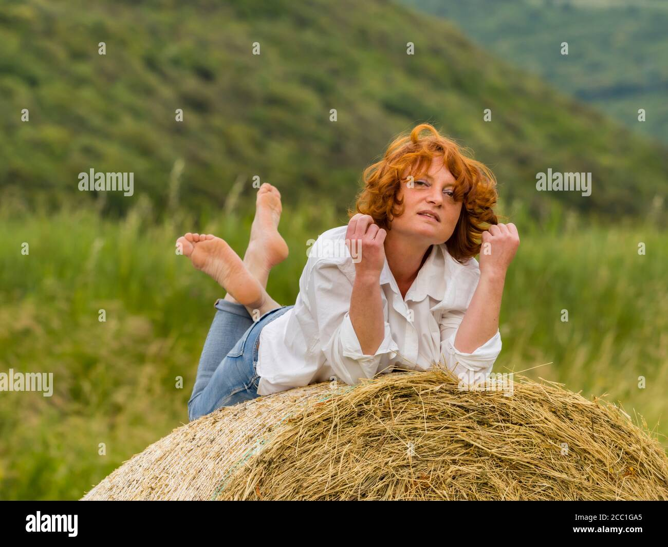 Redhaired woman on hay haystack eyeshot eyes eye contact looking at camera like lazy Stock Photo