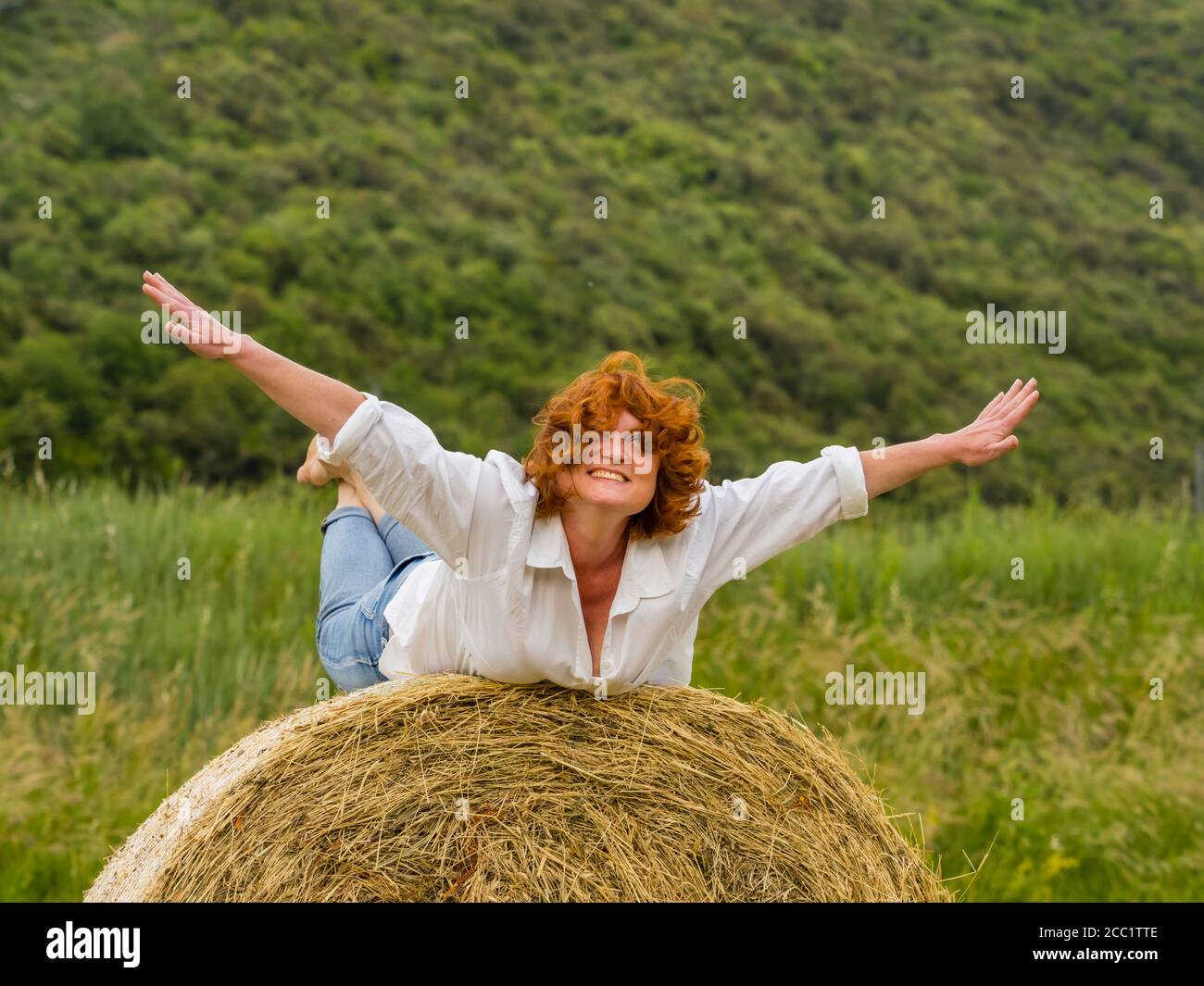Redhaired woman on hay haystack prone pretending to fly flying spreading spread hands arms away eyeshot eyes eye contact looking at camera Stock Photo