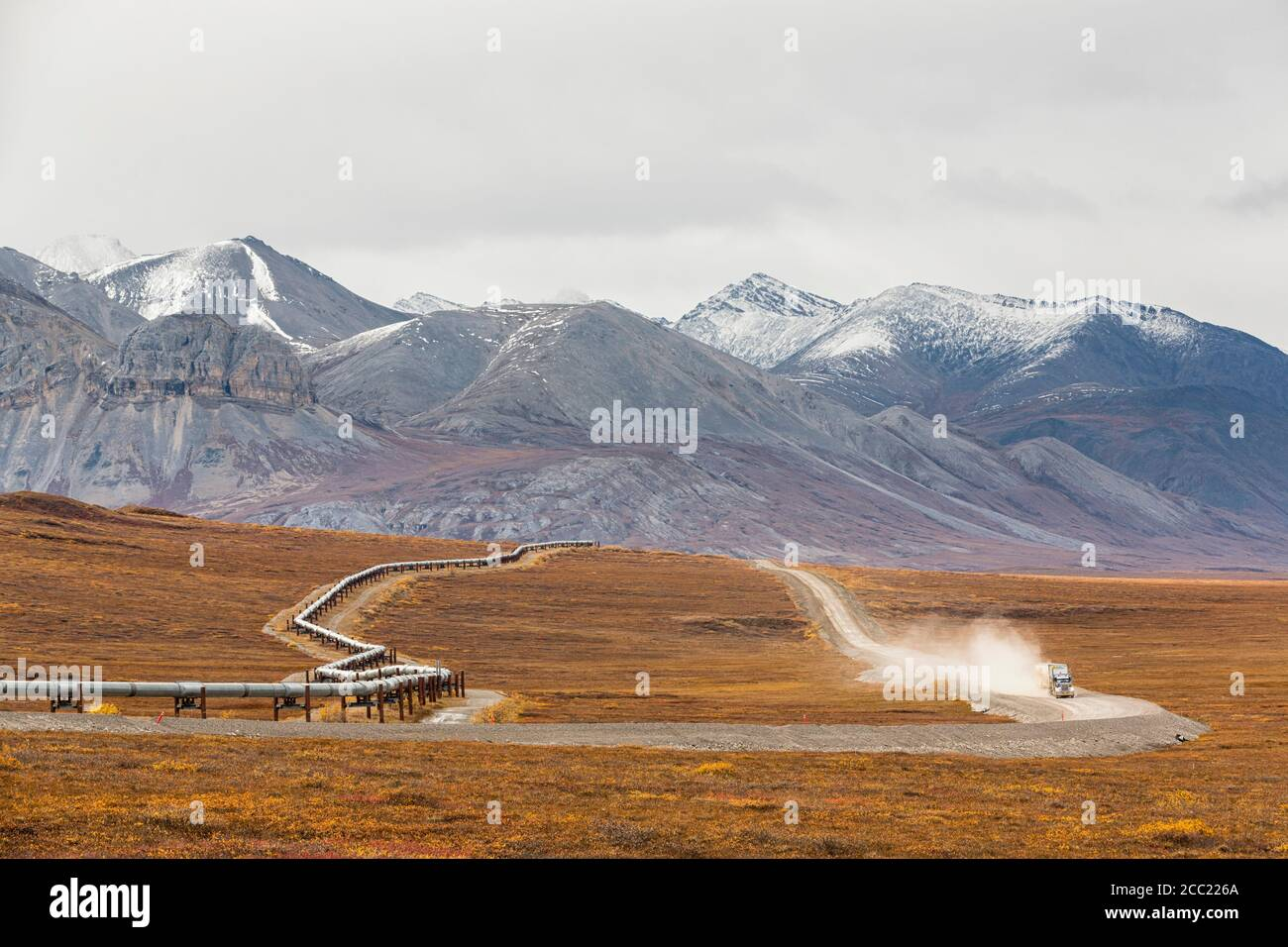 USA, Alaska, View of Trans Alaska Pipeline System along Dalton Highway with truck in autumn and Brooks Range Stock Photo