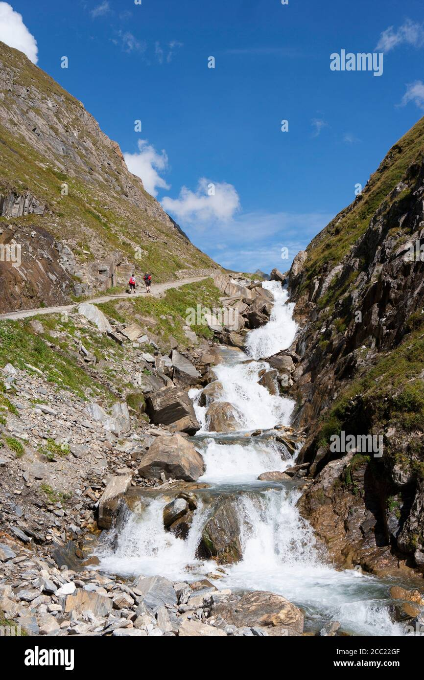 Italy, View of Pfunderer Berge with hikers walking near stream Stock Photo