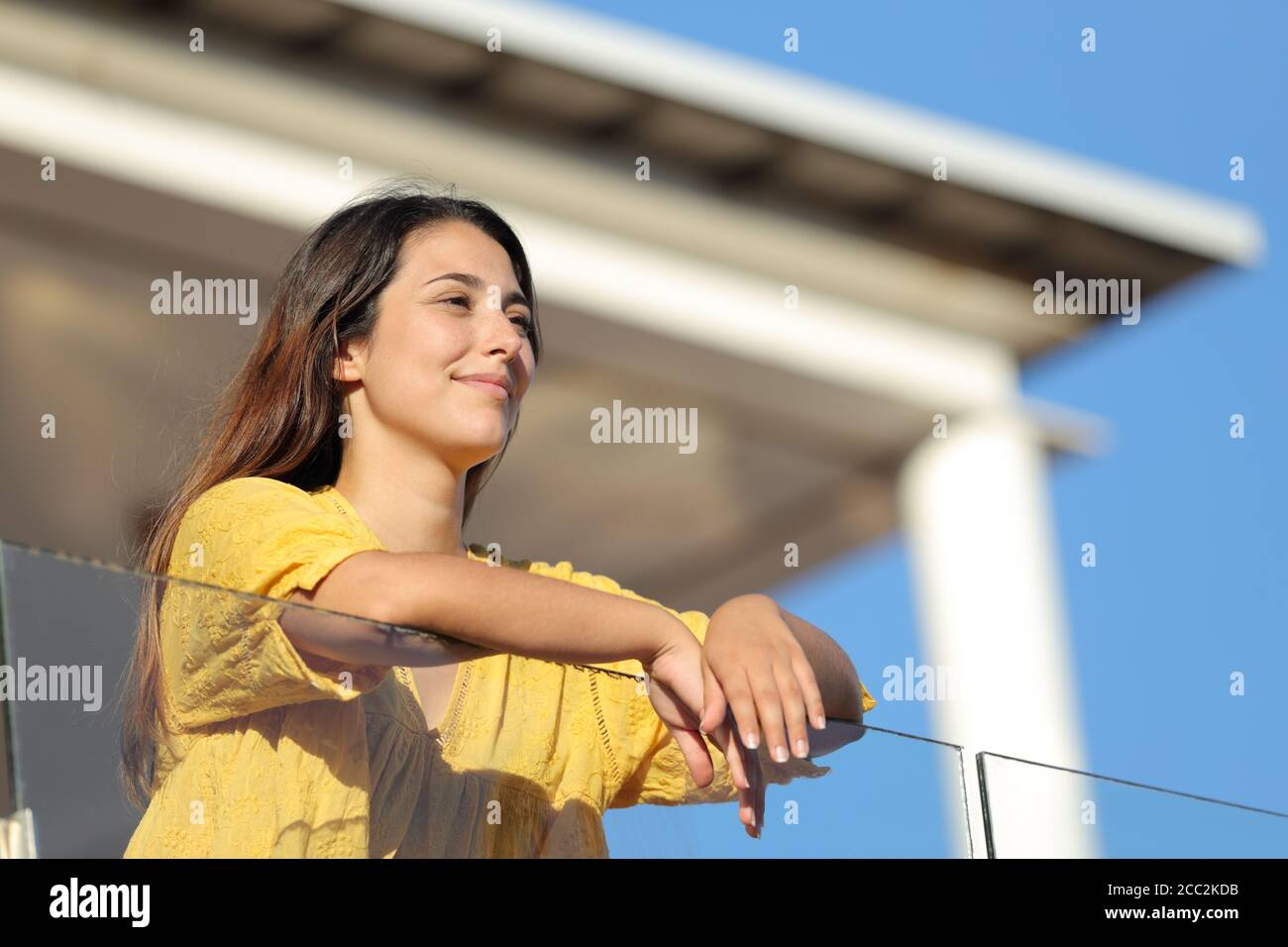 Satisfied woman in yellow contemplating views in a balcony on summer Stock Photo