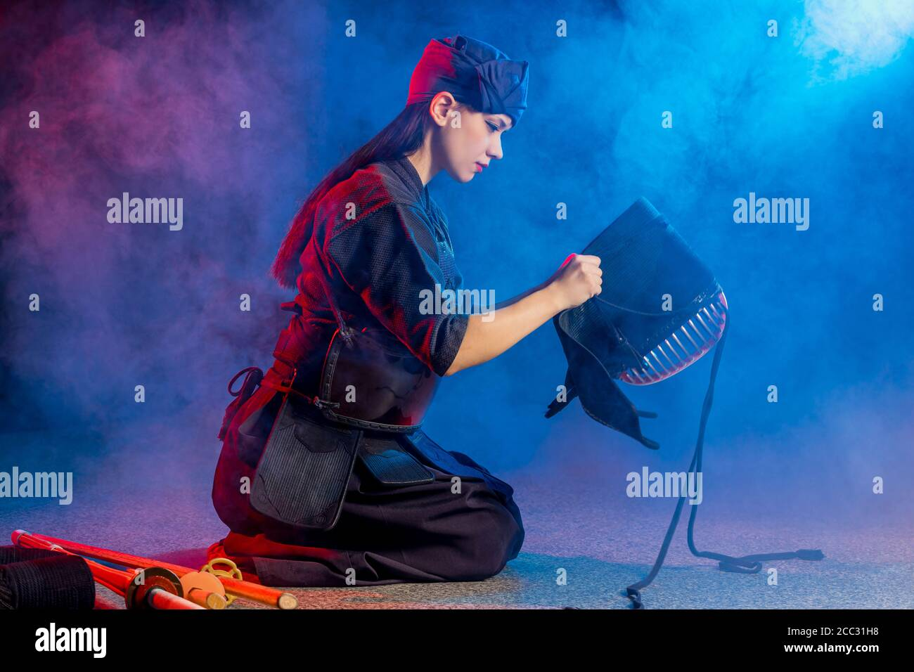 cuacasian kendo female wearing protective helmet on head before practicing fight. traditional japanese martial arts concept Stock Photo