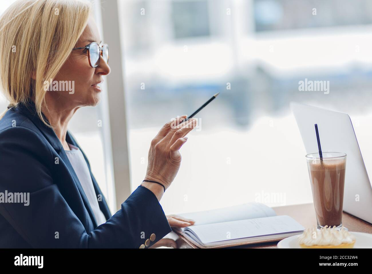 talented psychologist consulting a client in the cafe. close up side view photo. copy space. old smart woman instructing a customer Stock Photo