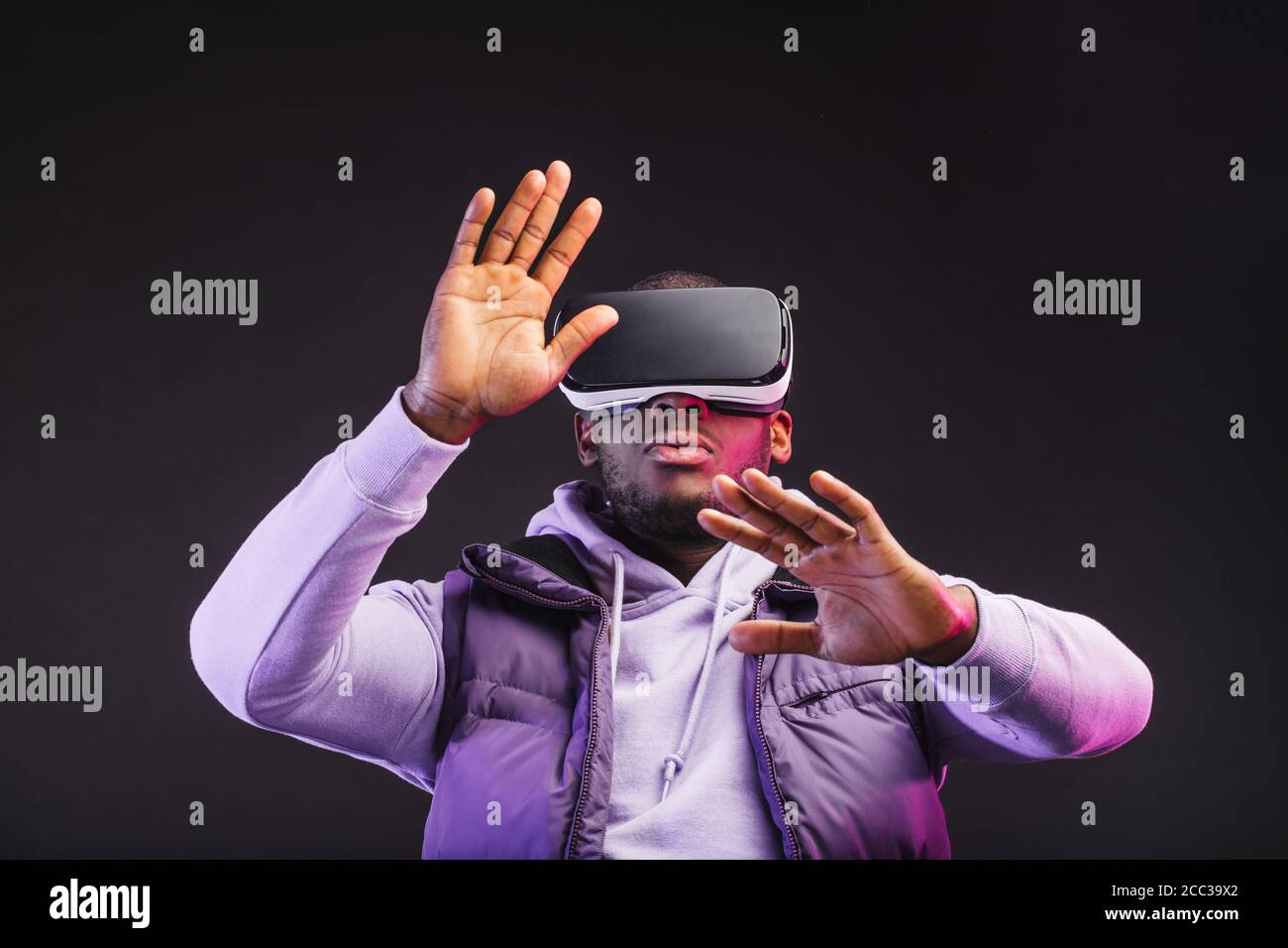 Young dark-skinned man dressed in outdoor wear having on head mobile virtual reality headset for playing 3D game but Mankind meets a new era of contro Stock Photo