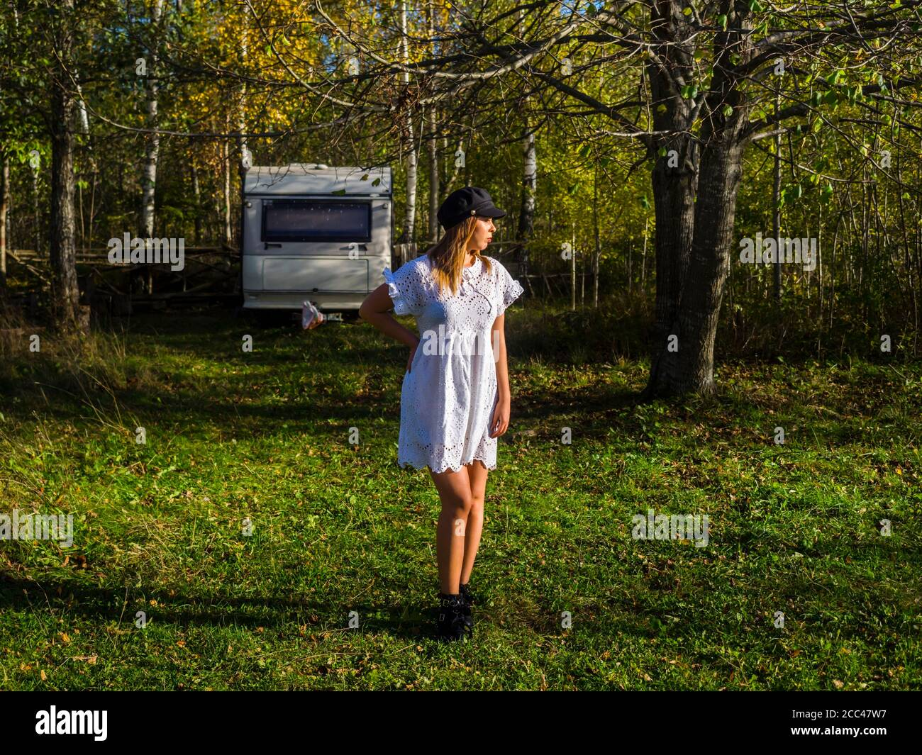 Teengirl standing in nature before caravan can travel travelling sleeping living vehicle looking aside away serious wearing short White robe clothing Stock Photo