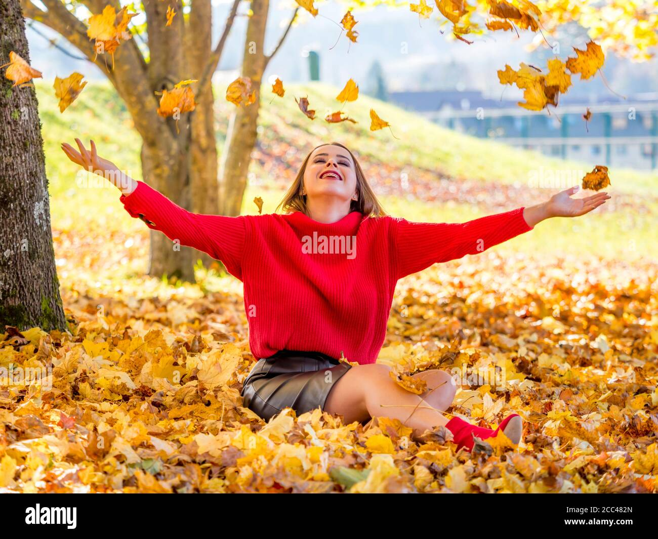 Teengirl in park nature Autumn Fall season seasonal conceptual concept throwing leaves above head up upwards away happy smiling spread arms hands Stock Photo