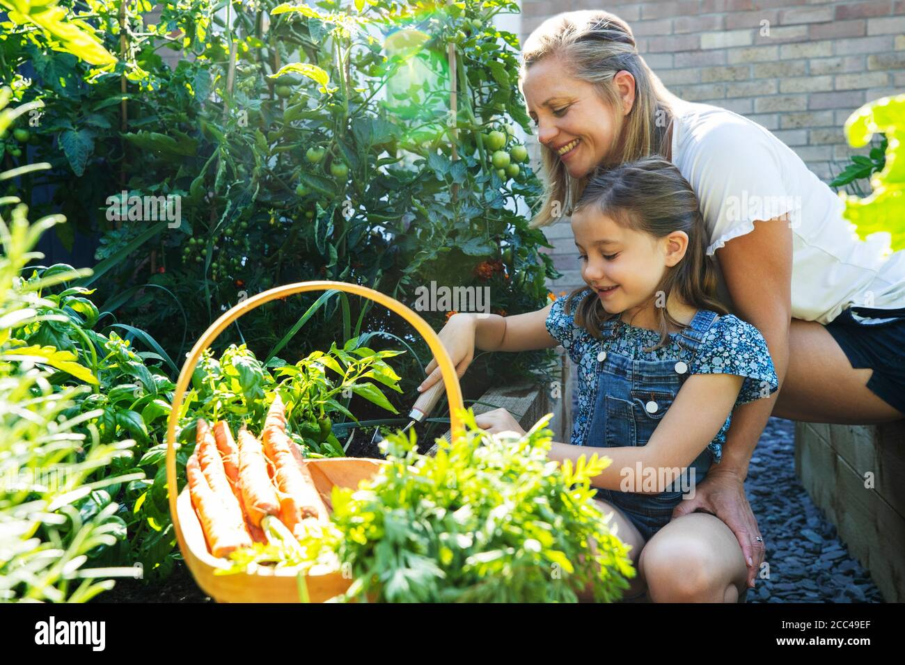 Mother And Daughter Digging In Raised Vegetable Beds At Home Stock Photo