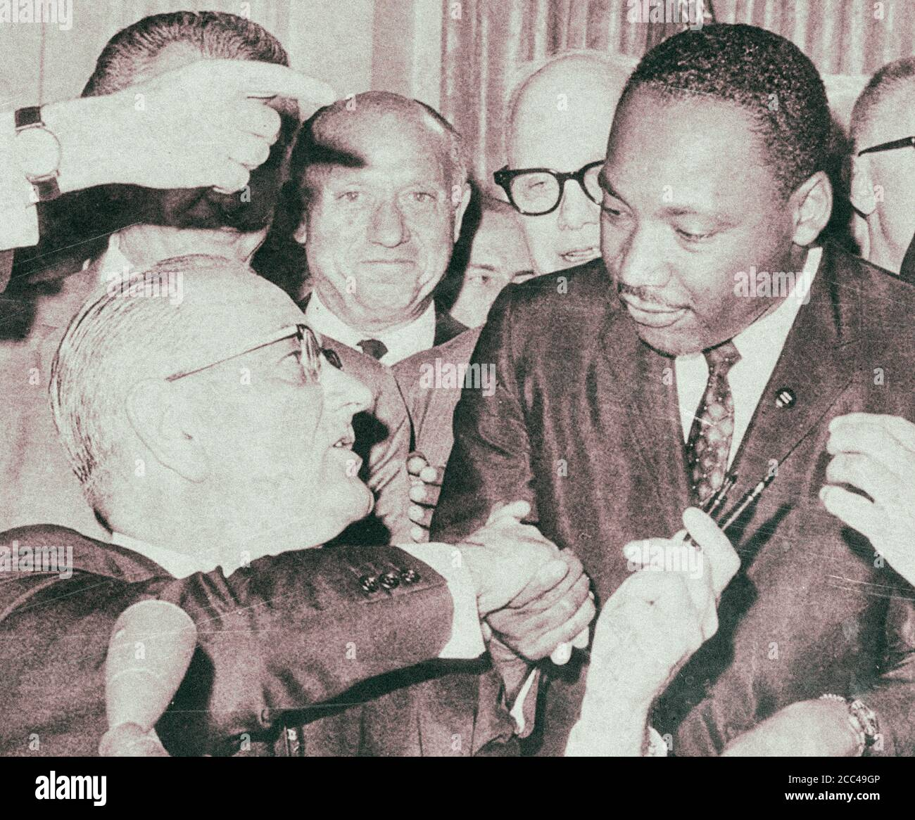 President Lyndon Johnson shakes hands with Reverend Martin Luther King, Jr., on July 3, 1964 in Washington, District of Columbia, after handing him a Stock Photo