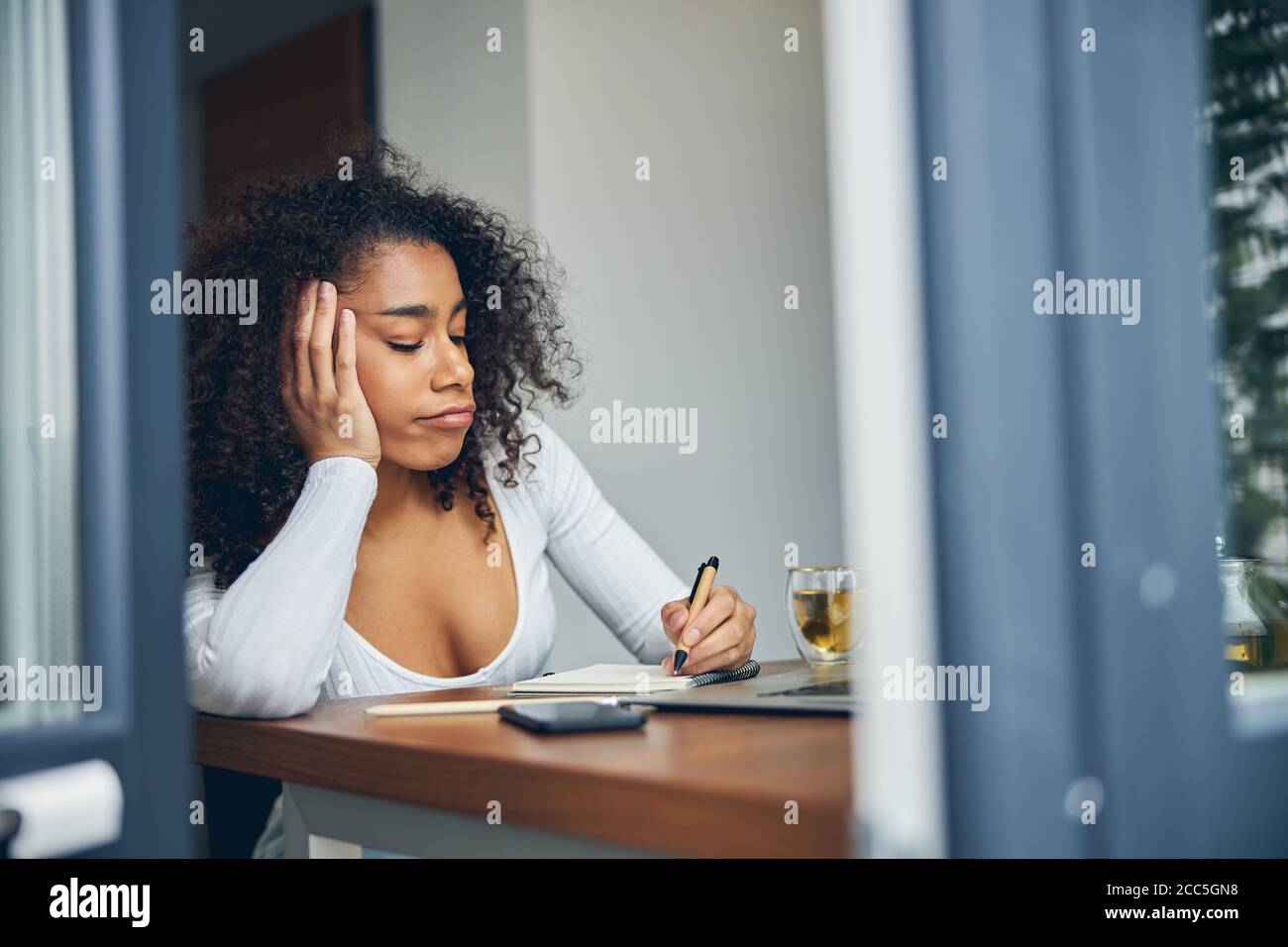 Beautiful African American woman sitting and writing Stock Photo