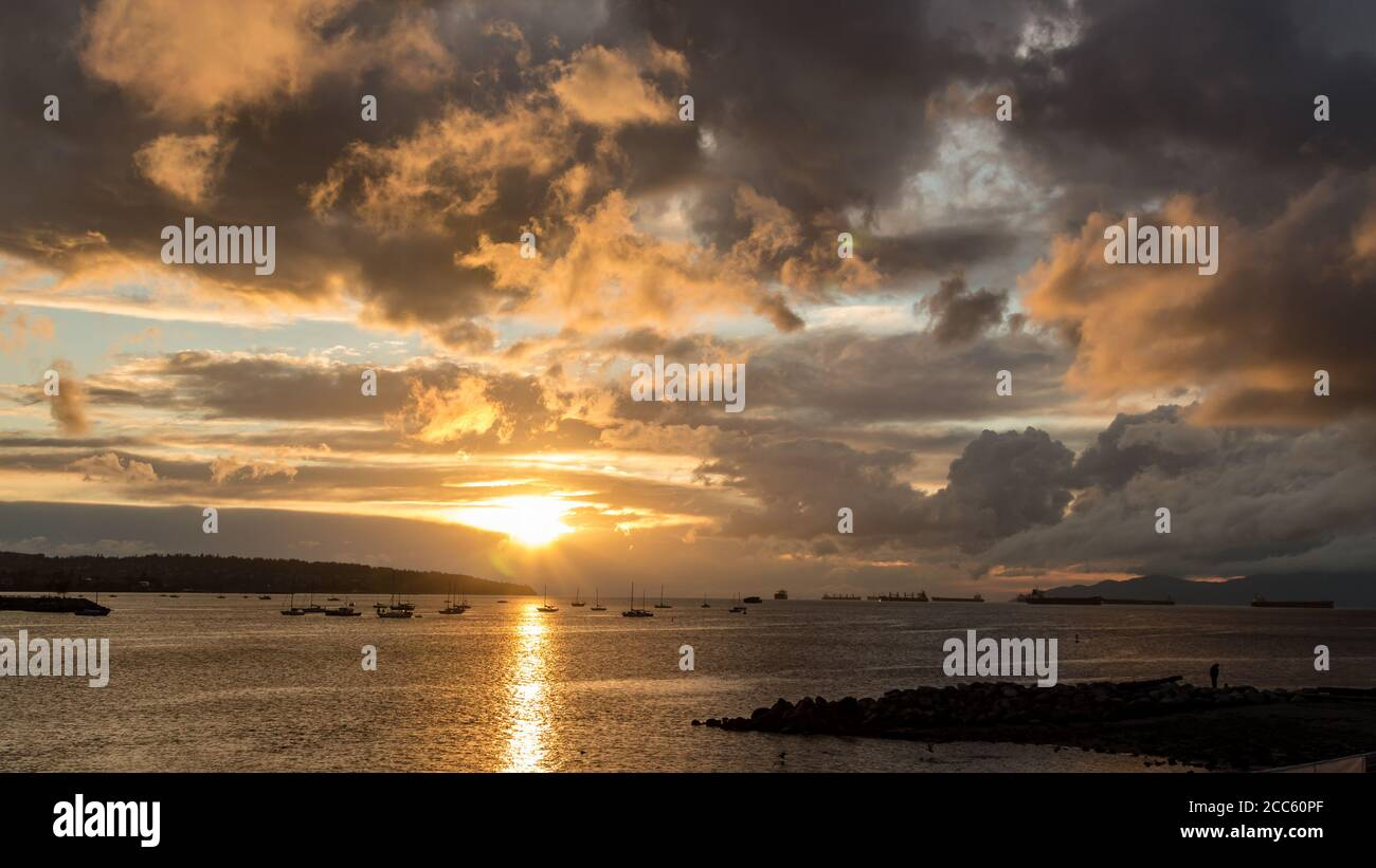 Golden sunset cloud sky ocean view at English Bay, Vancouver, BC, Canada Stock Photo
