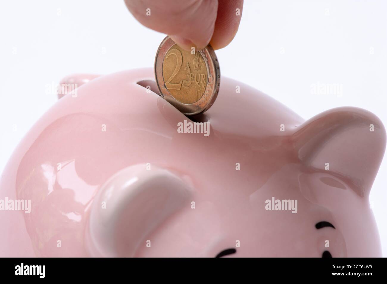 Hand putting a 2 euro coin into a piggy bank. Saving money and home finances concept. White background Stock Photo