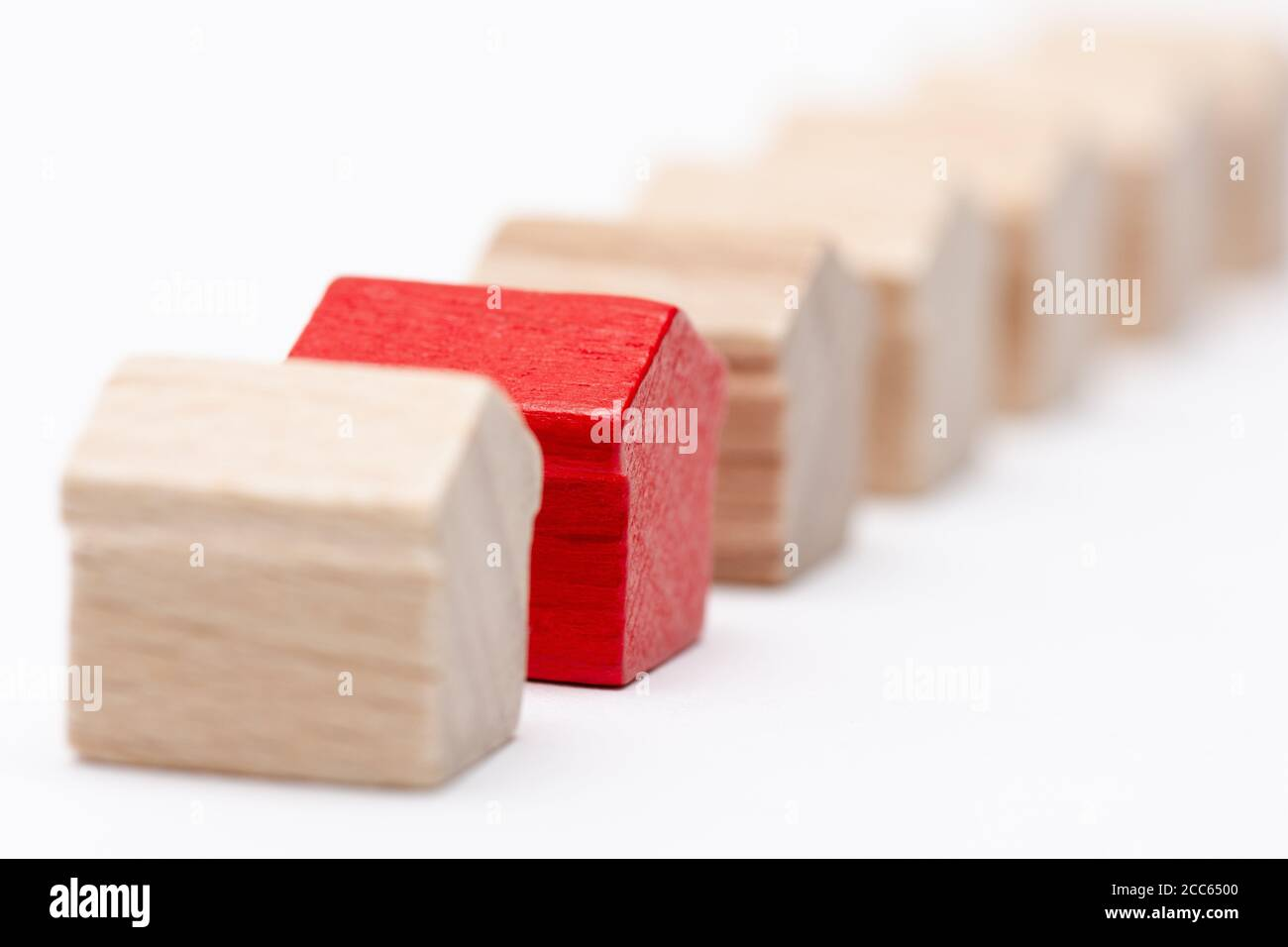 Tiny wooden toy houses in a row, one of them painted red, white background Stock Photo