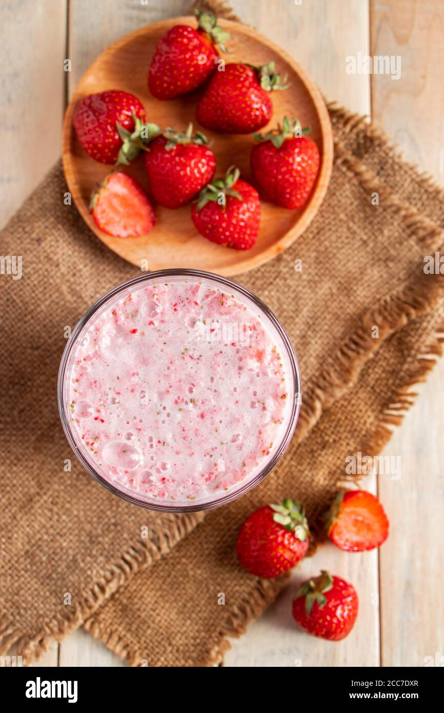 Fresh milkshake with strawberries. Summer drink with berries in a glass on a wooden background. Vertical photo Stock Photo