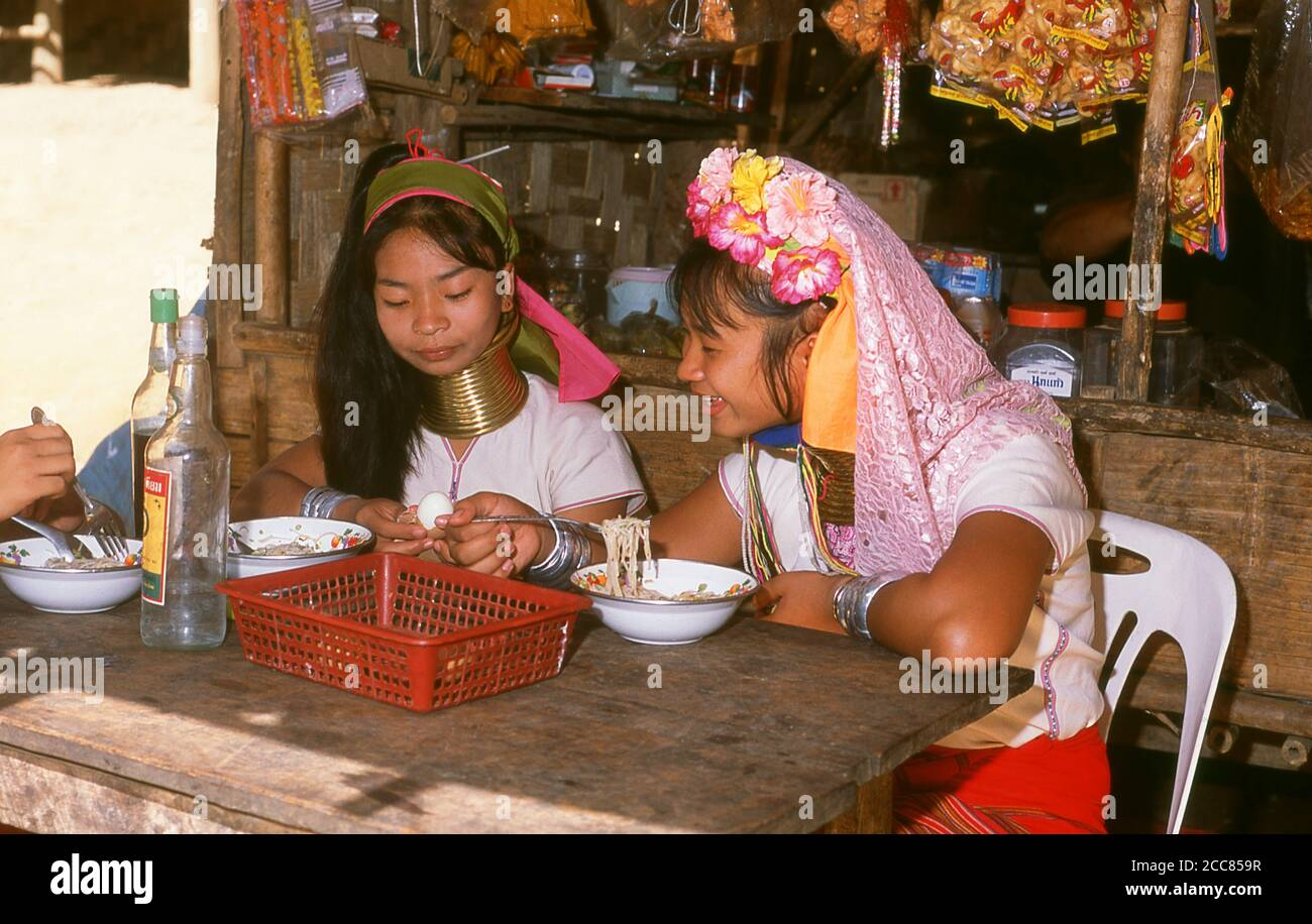 Thailand: Padaung (Long Neck Karen) women eating noodles in a village near Mae Hong Son, northern Thailand. The Padaung or Kayan Lahwi or Long Necked Karen are a subgroup of the Kayan, a mix of Lawi, Kayan and several other tribes. Kayan are a subgroup of the Red Karen (Karenni) people, a Tibeto-Burman ethnic minority of Burma (Myanmar). Stock Photo