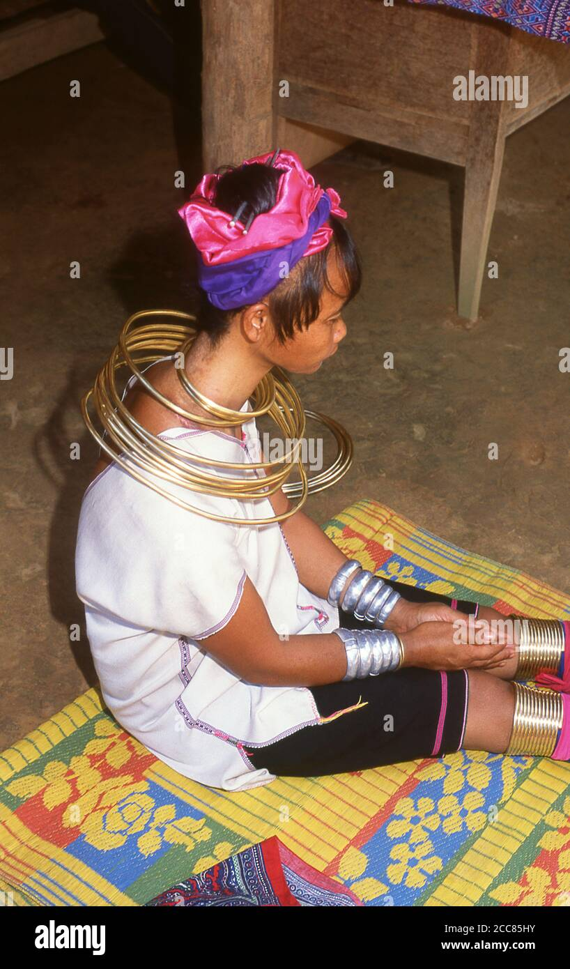 Thailand: A Padaung (Long Neck Karen) woman removing her neck rings for cleaning, village near Mae Hong Son. The Padaung or Kayan Lahwi or Long Necked Karen are a subgroup of the Kayan, a mix of Lawi, Kayan and several other tribes. Kayan are a subgroup of the Red Karen (Karenni) people, a Tibeto-Burman ethnic minority of Burma (Myanmar). Stock Photo