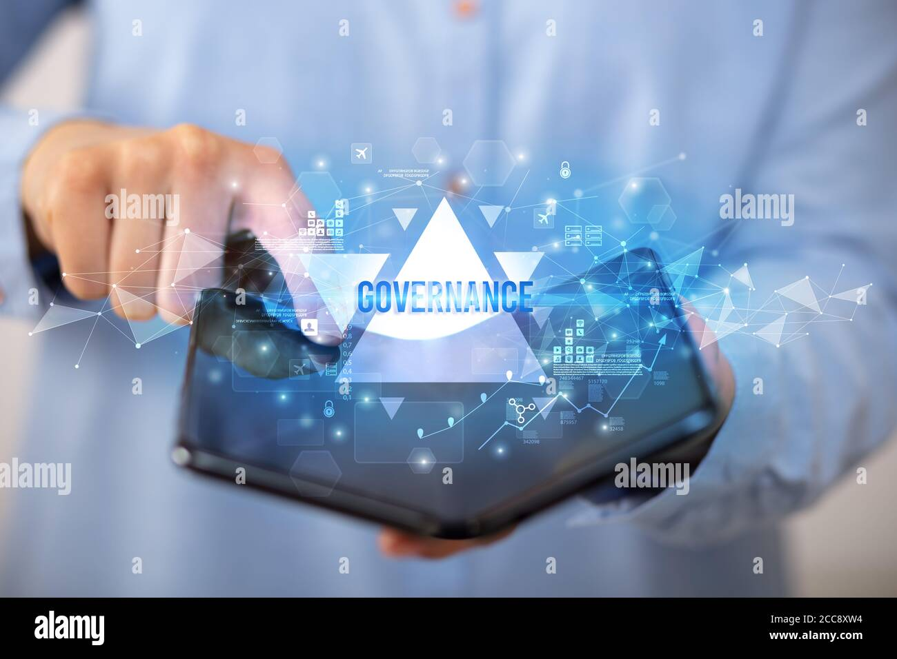 Businessman holding a foldable smartphone with GOVERNANCE inscription, business concept Stock Photo