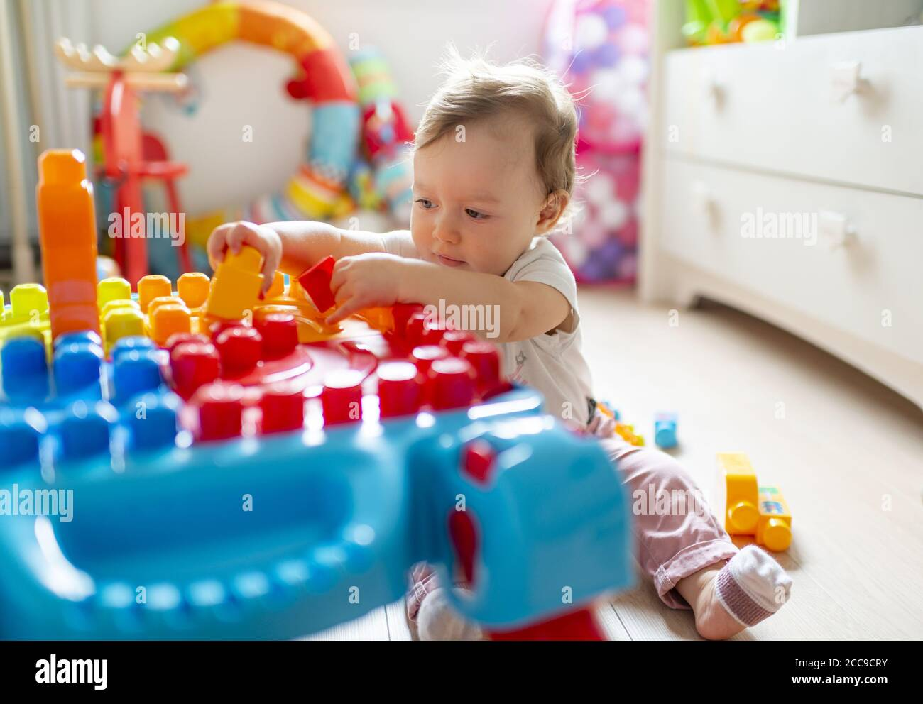 Baby girl (16 months) sitting on the floor and playing in her bedroom with colourful Mega Bloks® plastic blocks near her white wooden chest of drawers Stock Photo