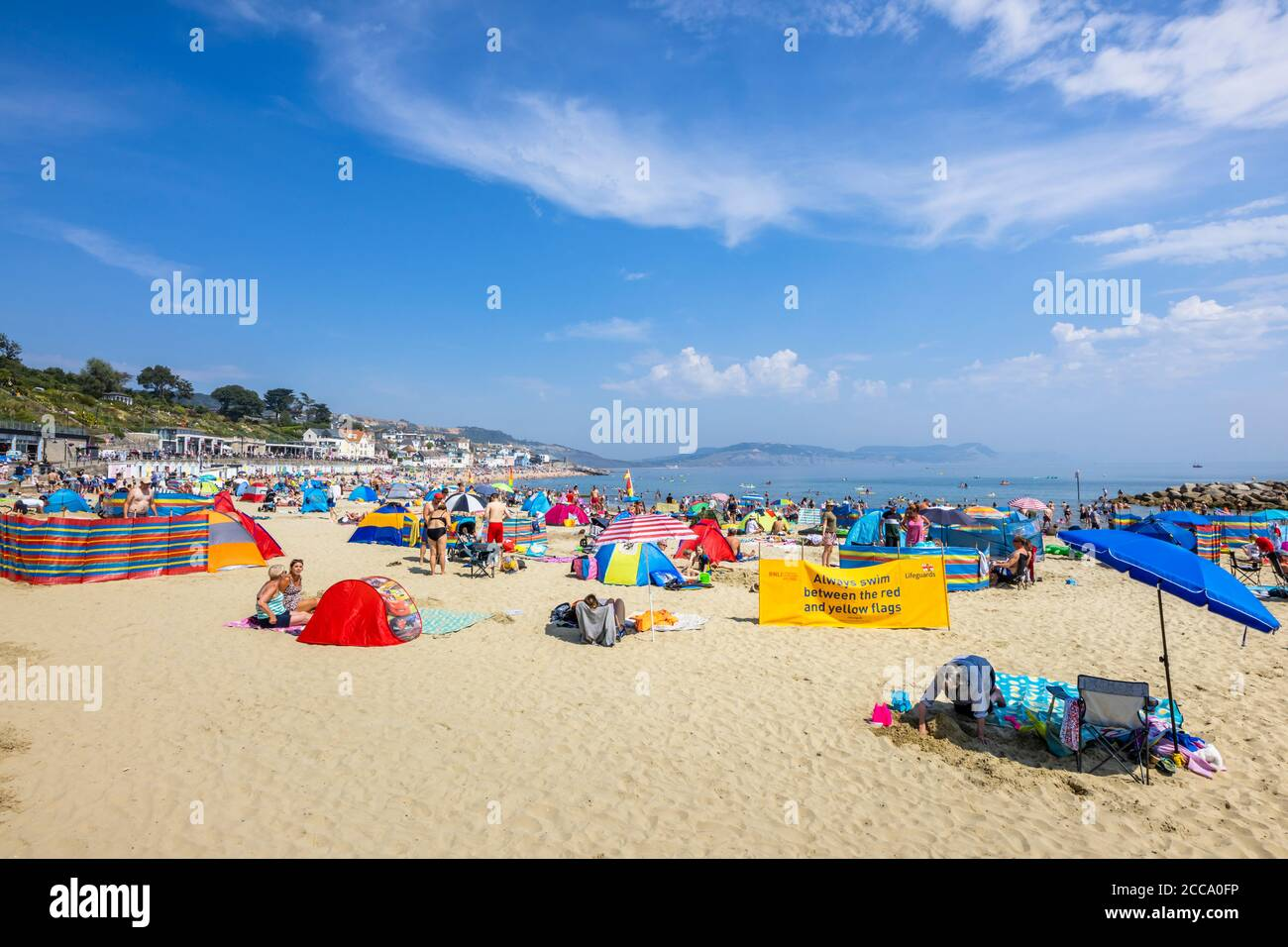 The crowded beach and seafront in high season at Lyme Regis, a popular seaside holiday resort on the Jurassic Coast in Dorset, south-west England Stock Photo