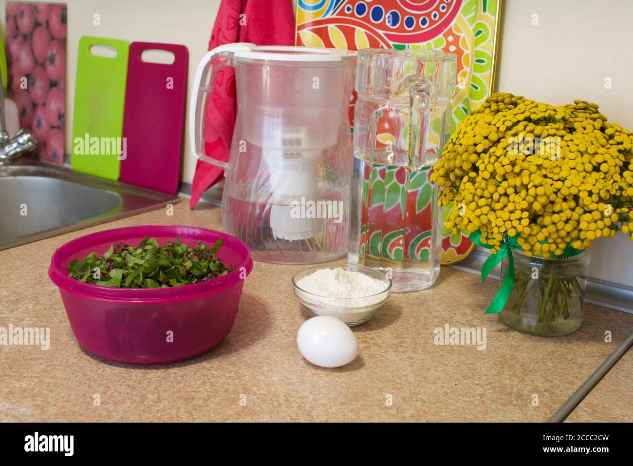 Preparation of cutlets from beet tops. Container with crushed beet tops, flour and chicken egg on the countertop. Regional food. Stock Photo