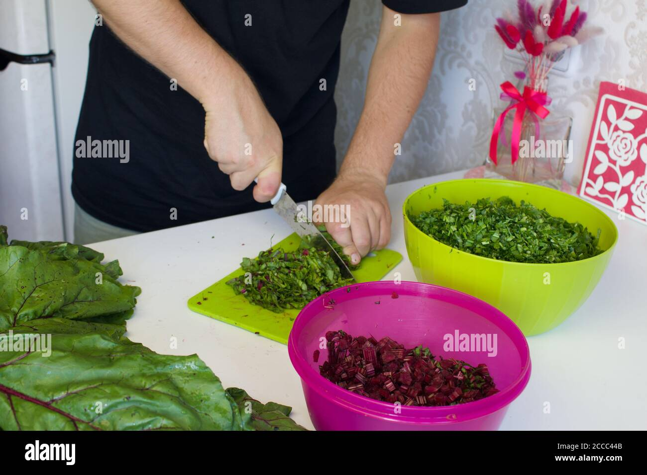 The man cut the tops of beets on a cutting Board. Next to it on the surface of the table are parsley and beet tops. In the container, crushed parsley Stock Photo