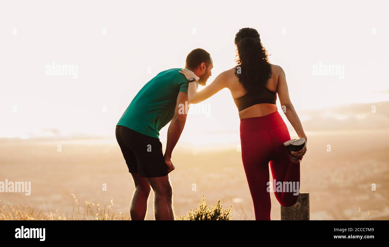 Fitness man and woman doing warm up exercises. Rear view of a female athlete stretching her muscles standing outdoors with her running mate. Stock Photo