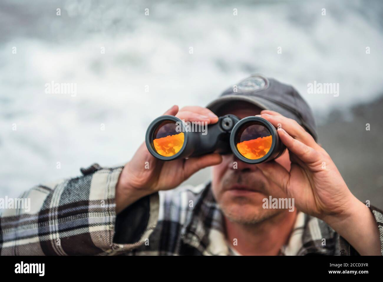 Close up shot of man looking through binoculars with not visible face. Stock Photo