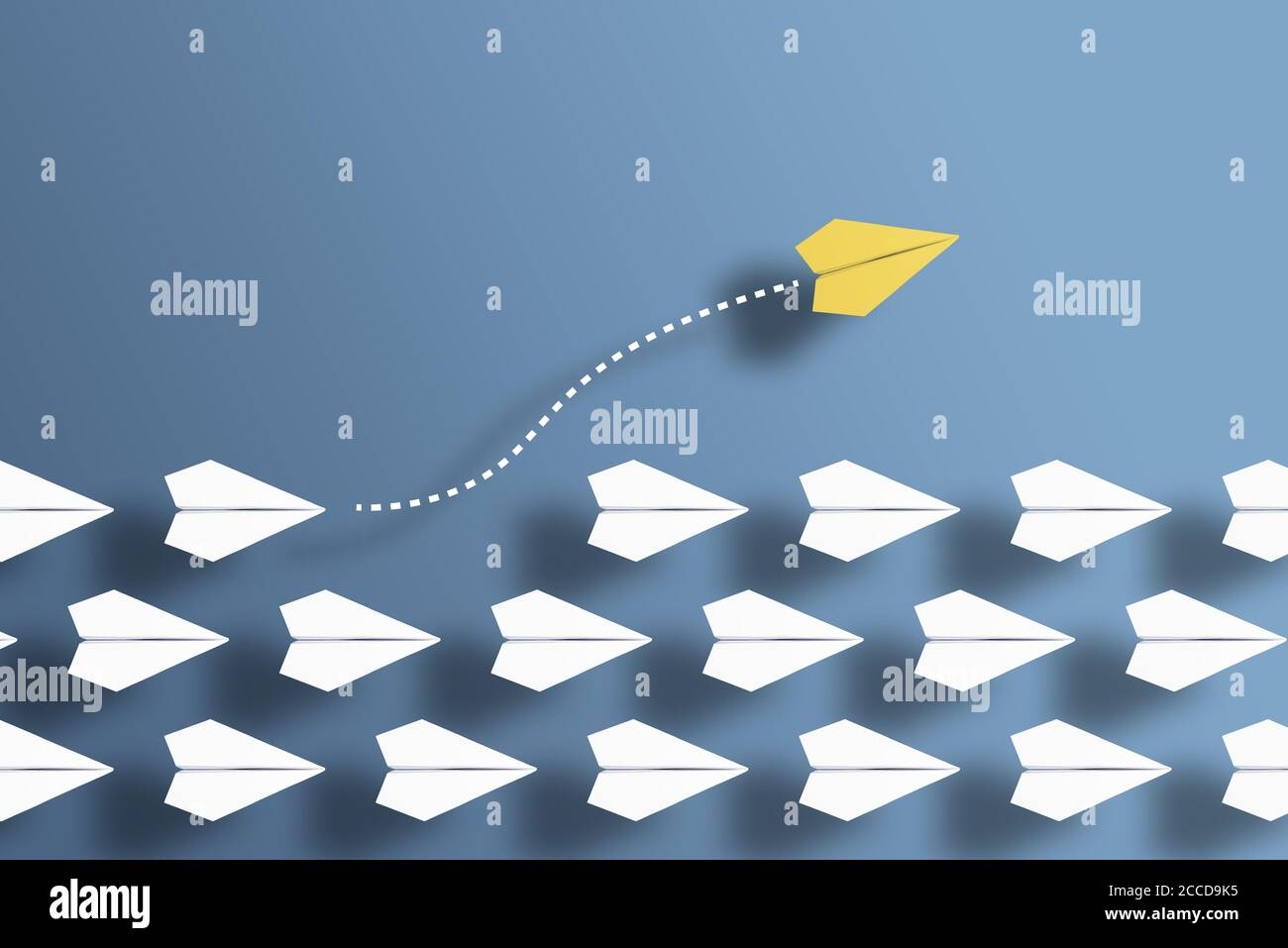 paper planes in a row on blue background and one paper glider going in different direction, breaking new ground and stepping out of the line concept Stock Photo