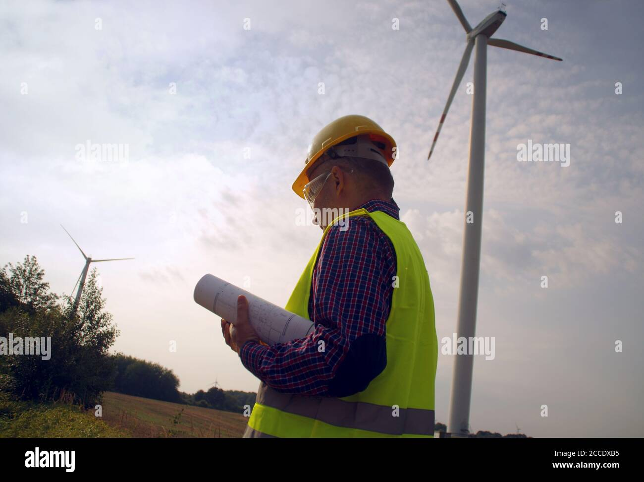 Engineer in a wind turbine. A man in a helmet supervises the operation of the electric windmills. Ecology and renewable energy sources concept. Stock Photo
