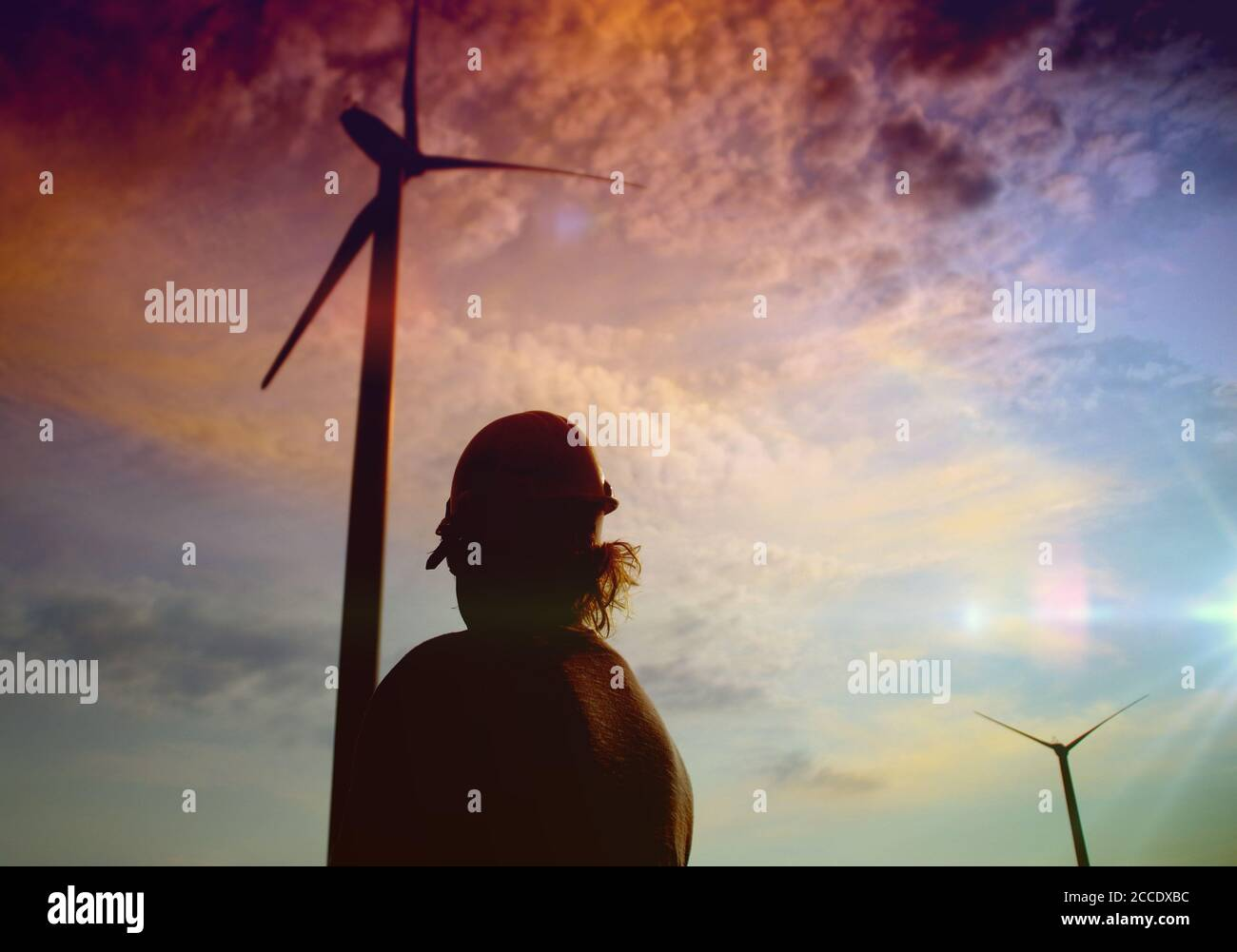 Engineer in a wind turbine. A woman in a helmet supervises the operation of the electric windmills. Ecology and renewable energy sources concept. Stock Photo