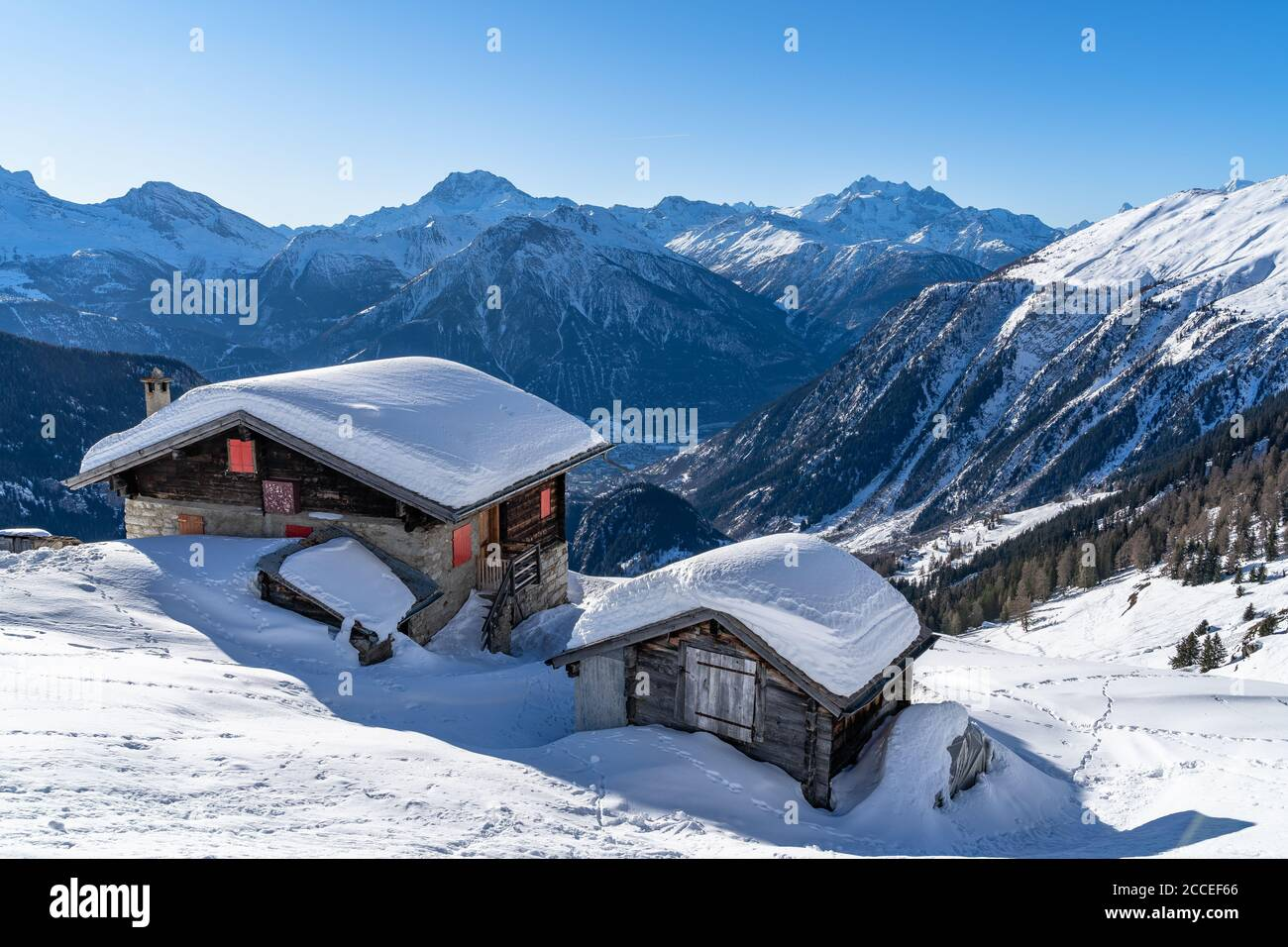 Europe, Switzerland, Valais, Belalp, snowed-in wooden huts against the mountain backdrop of the Valais Alps Stock Photo