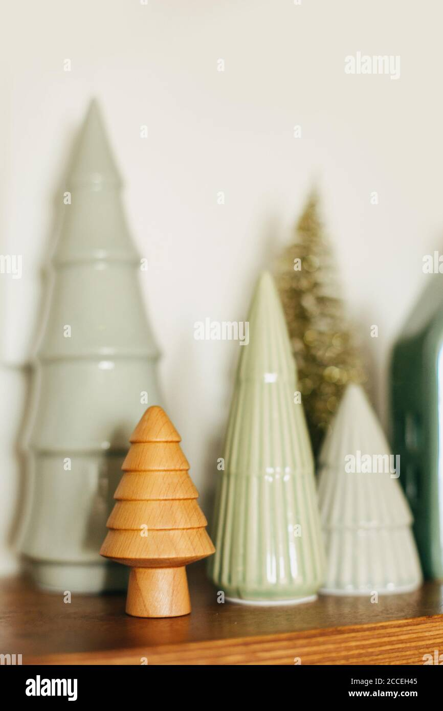 Modern Little Christmas Trees On Wooden Shelf Stylish Festive Decor Christmas Miniature Forest Wooden And Ceramic Trees Merry Christmas And Happy Stock Photo Alamy