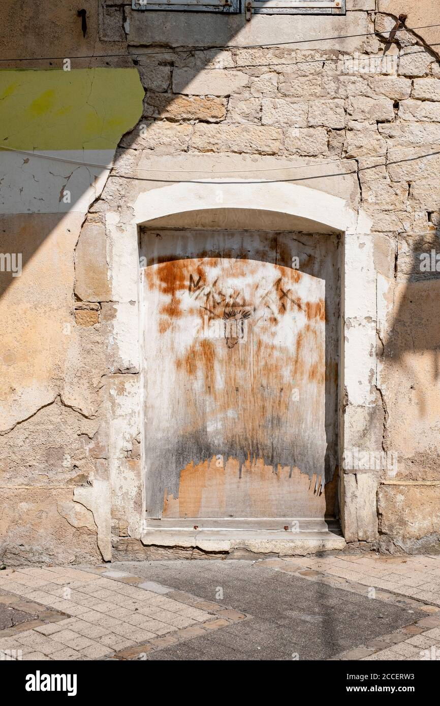 Weathered wooden door with graffiti on a natural stone facade with crumbling plaster Stock Photo