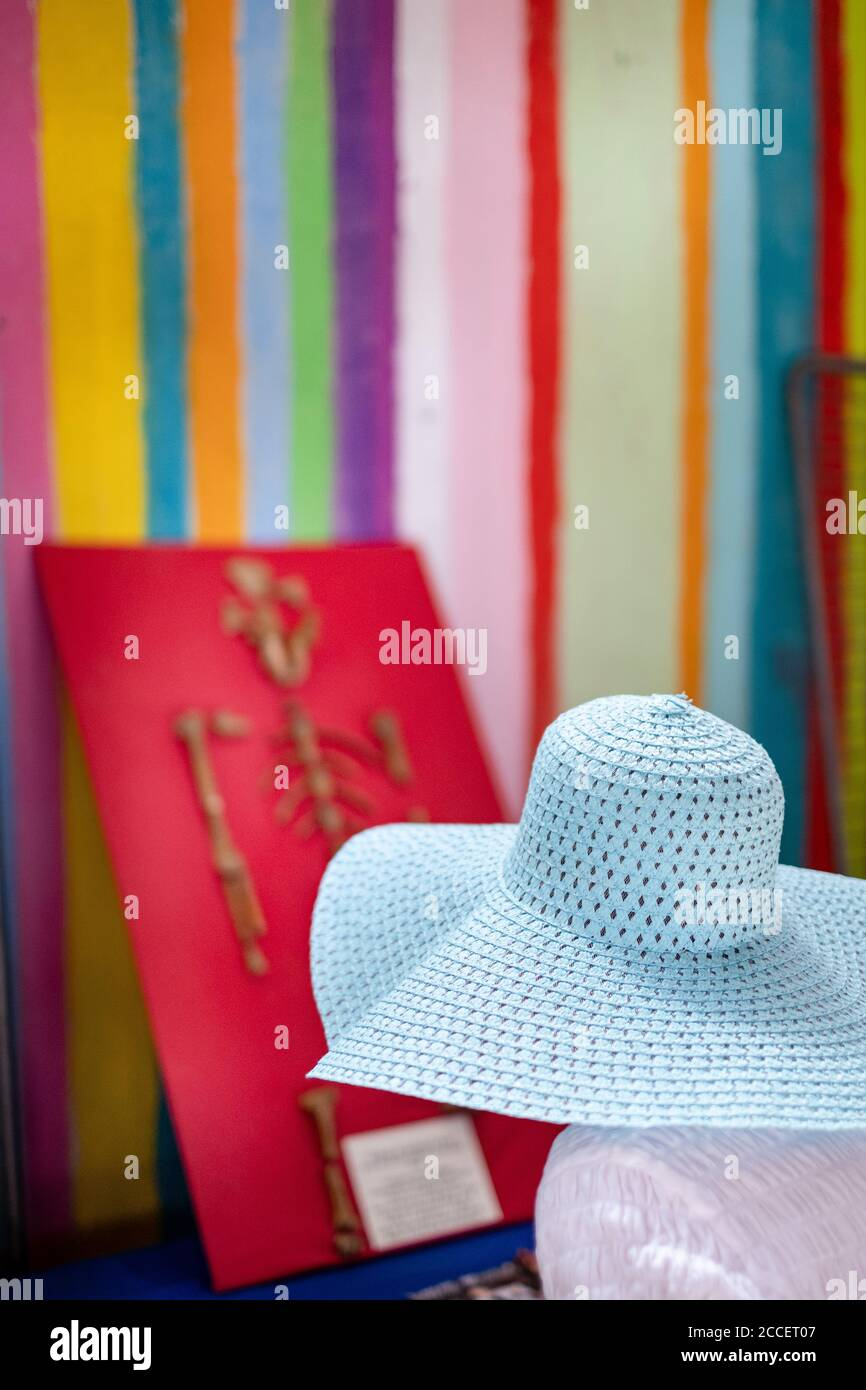 Anonymous lady with a floppy hat looks at a monkey skeleton on a striped wall Stock Photo