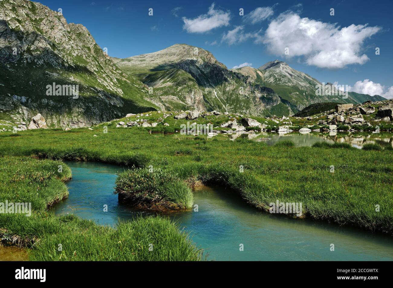 Majestic mountains landscape with blue deep river in green grassy valley. Beautiful wild nature Stock Photo