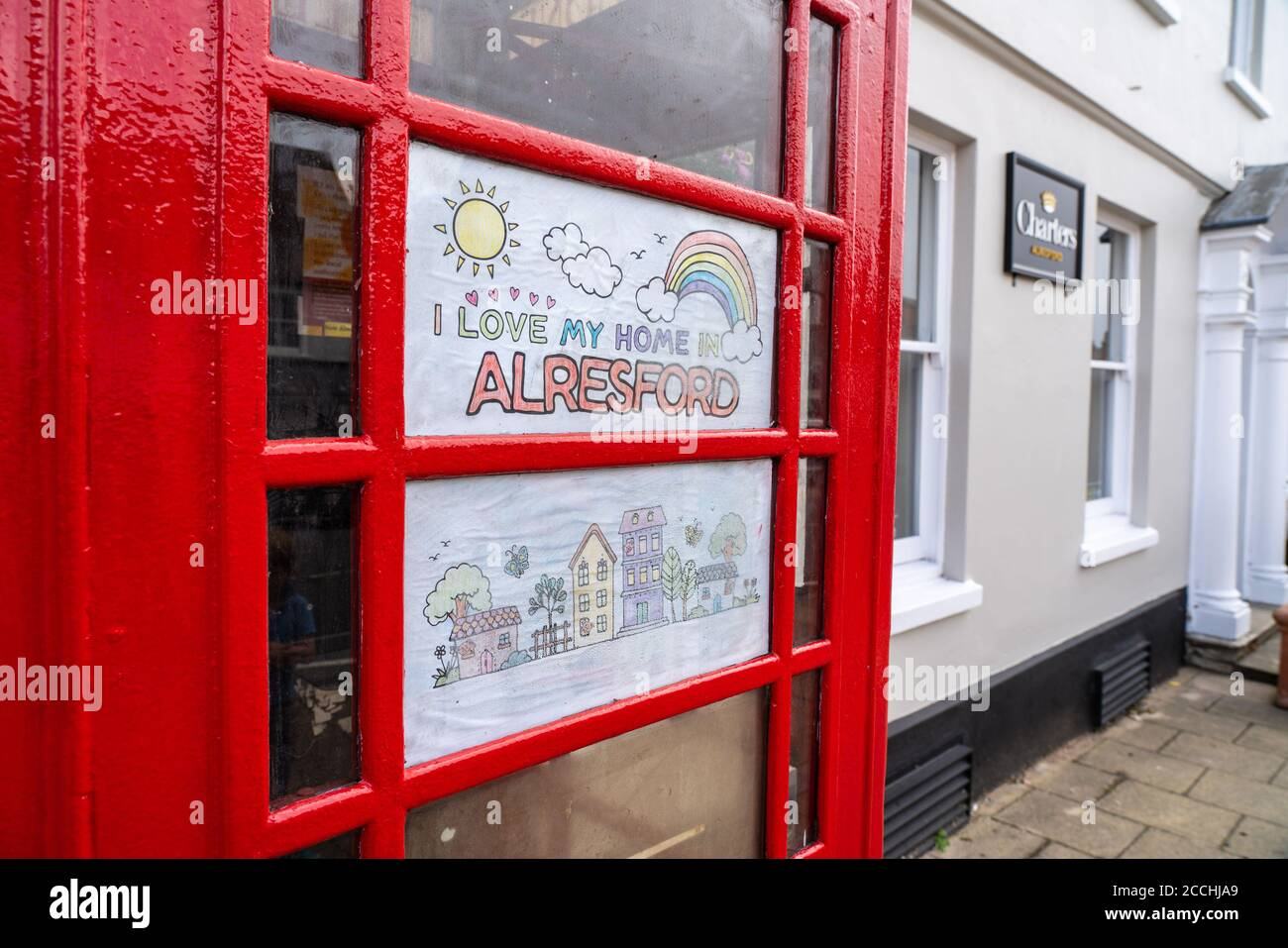 """""""I love my home in Alresford"""". Child's drawing in telephone box with rainbow. Spreading hope during Covid 19 crisis. Stock Photo"""