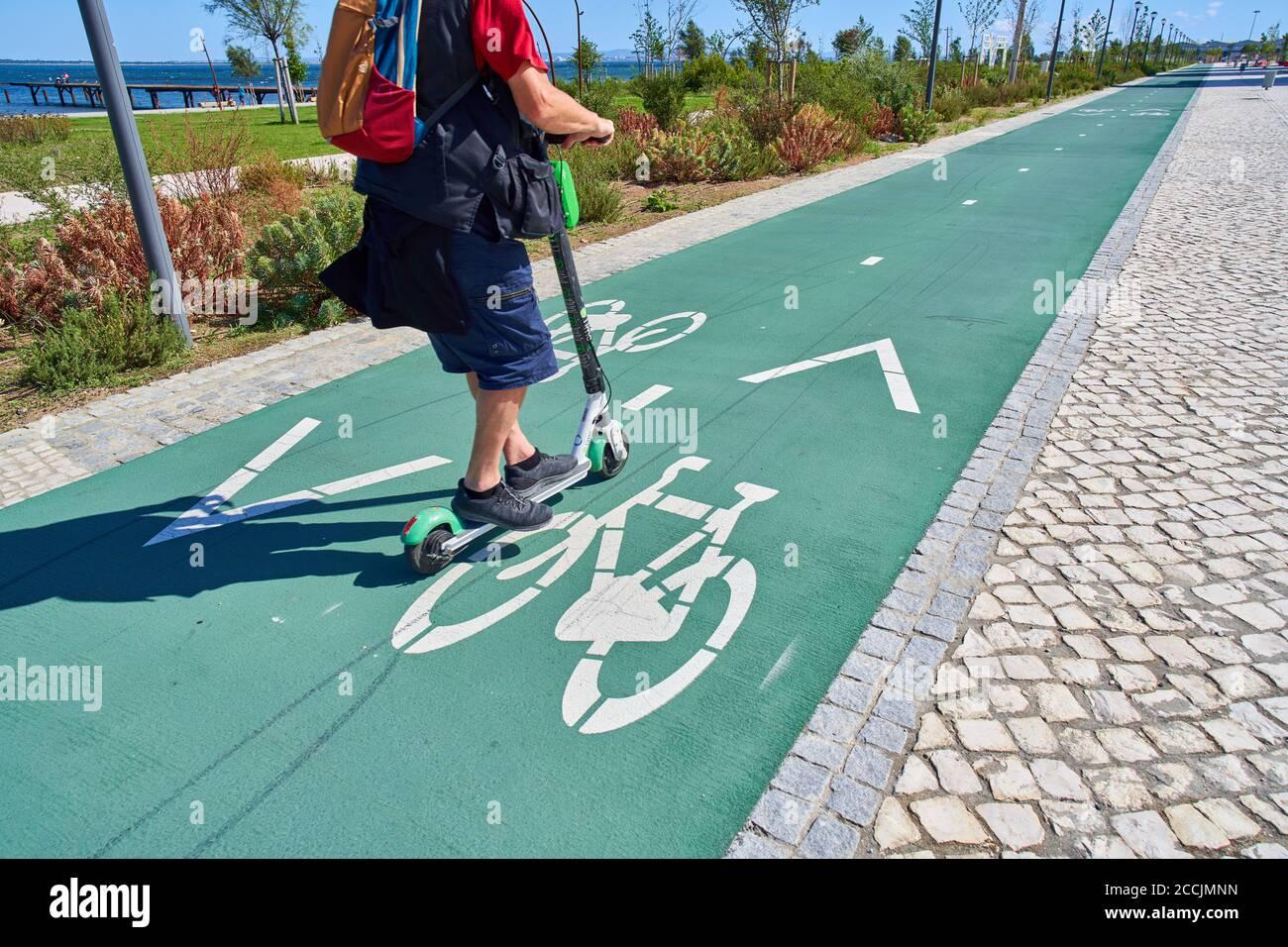Lisbon, Lissabon, Portugal, 16rd August 2020.  A man driving an e-scooter on a bicycle track. © Peter Schatz / Alamy Stock Photos Stock Photo