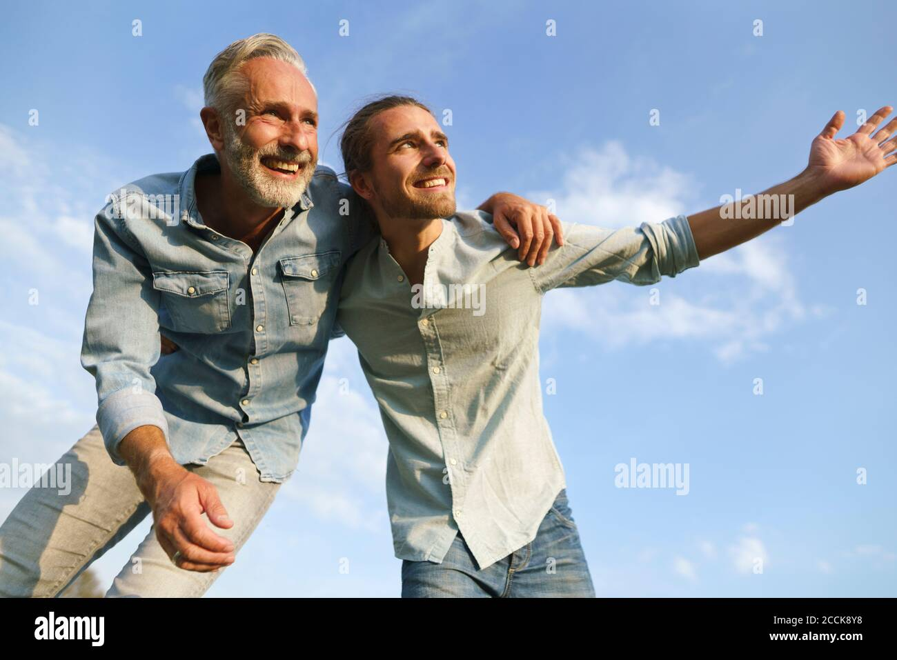 Carefree father with adult son under blue sky Stock Photo