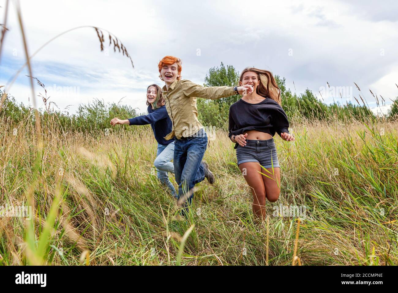 Summer holidays vacation happy people concept. Group of three friends boy and two girls running and having fun together outdoors. Picnic with friends on road trip in nature Stock Photo