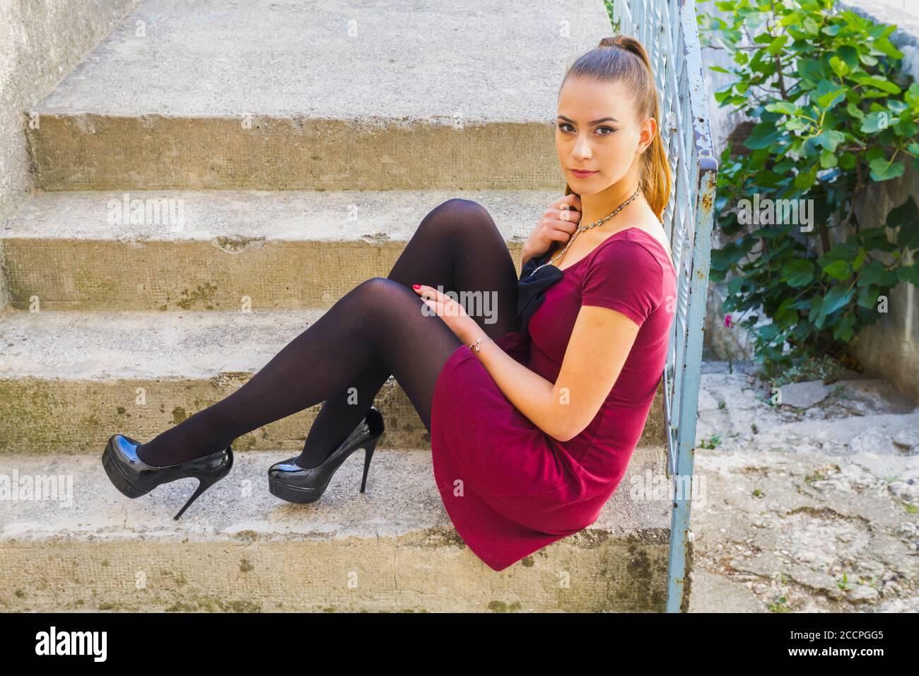 Teengirl legs heels Burgundy Red minidress and Black opaque nylon tights ponytail pony-tail Bruunete hair eyeshot eyes eye contact looking at camera Stock Photo