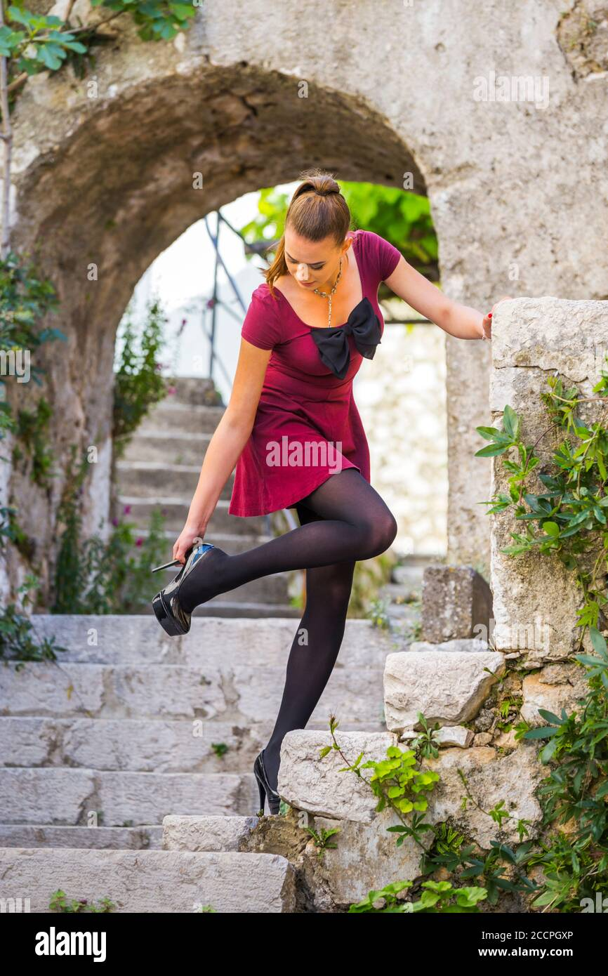 Teengirl legs heels Burgundy Red minidress and Black opaque nylon tights ponytail pony-tail Bruunete hair serious looking down away feel pain painful Stock Photo
