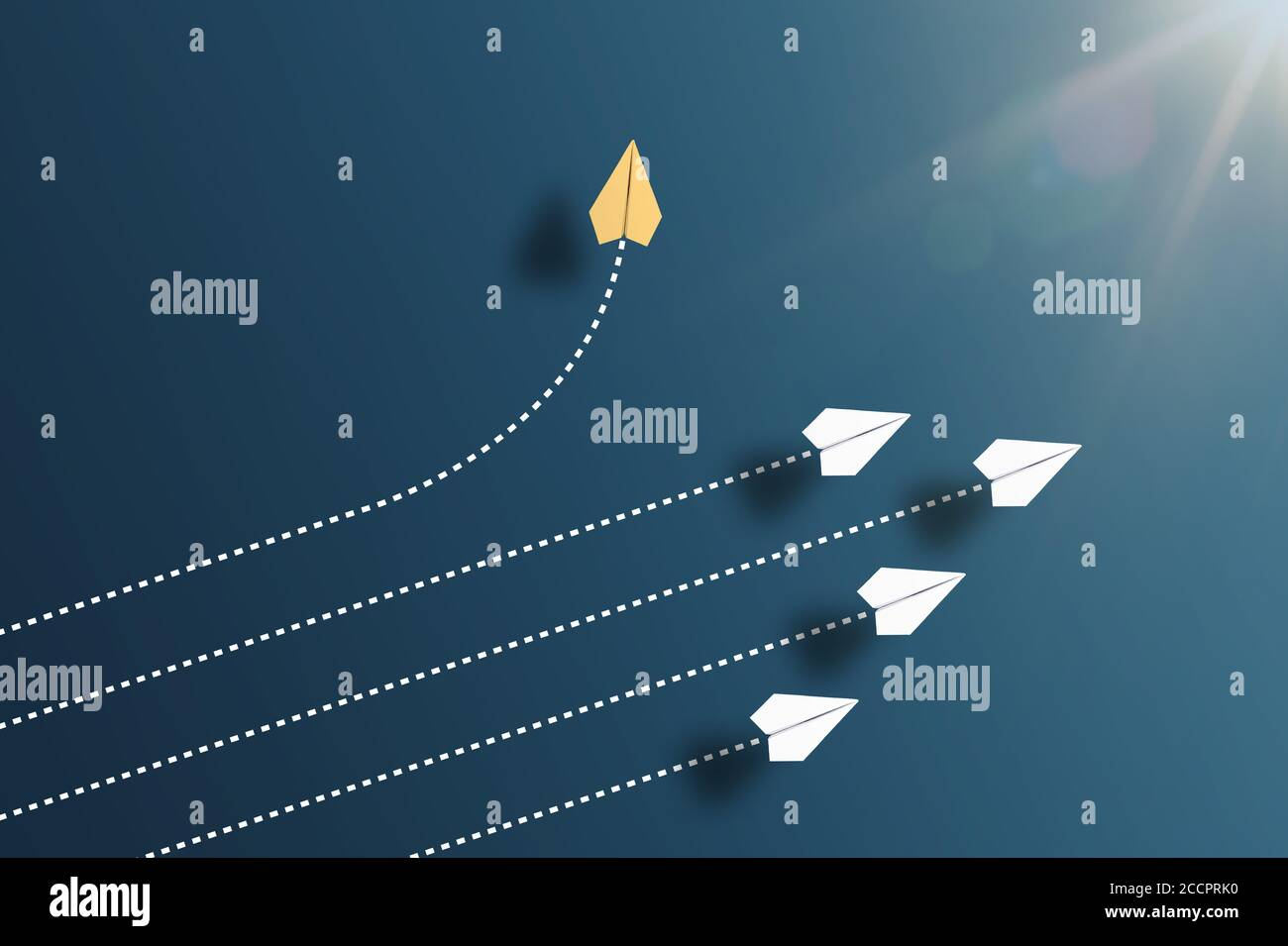 paper planes flying in formation in one direction on blue background and one paper glider going in different direction, breaking new ground and Stock Photo
