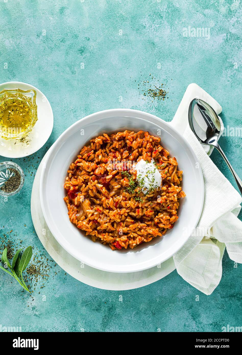 risotto with caramelized onions, tomatoes and coconut cream on a plate on the table. mix of Asian and Mediterranean cuisine Stock Photo