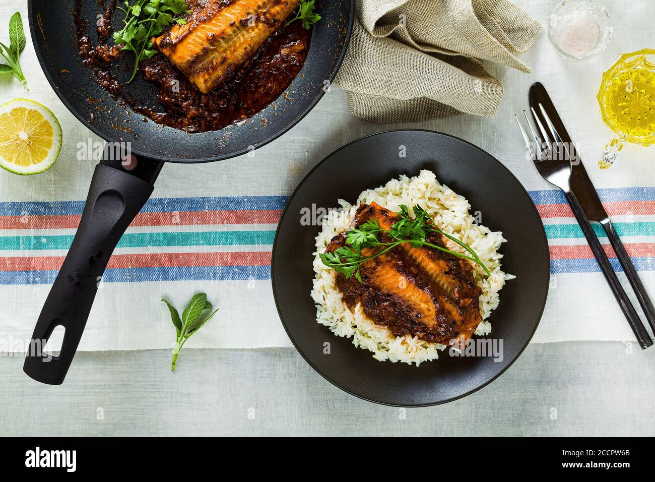 fillet of pink salmon in tomato-coconut sauce in a non-stick frying pan with parsley on a table with a linen tablecloth. healthy family food with basm Stock Photo